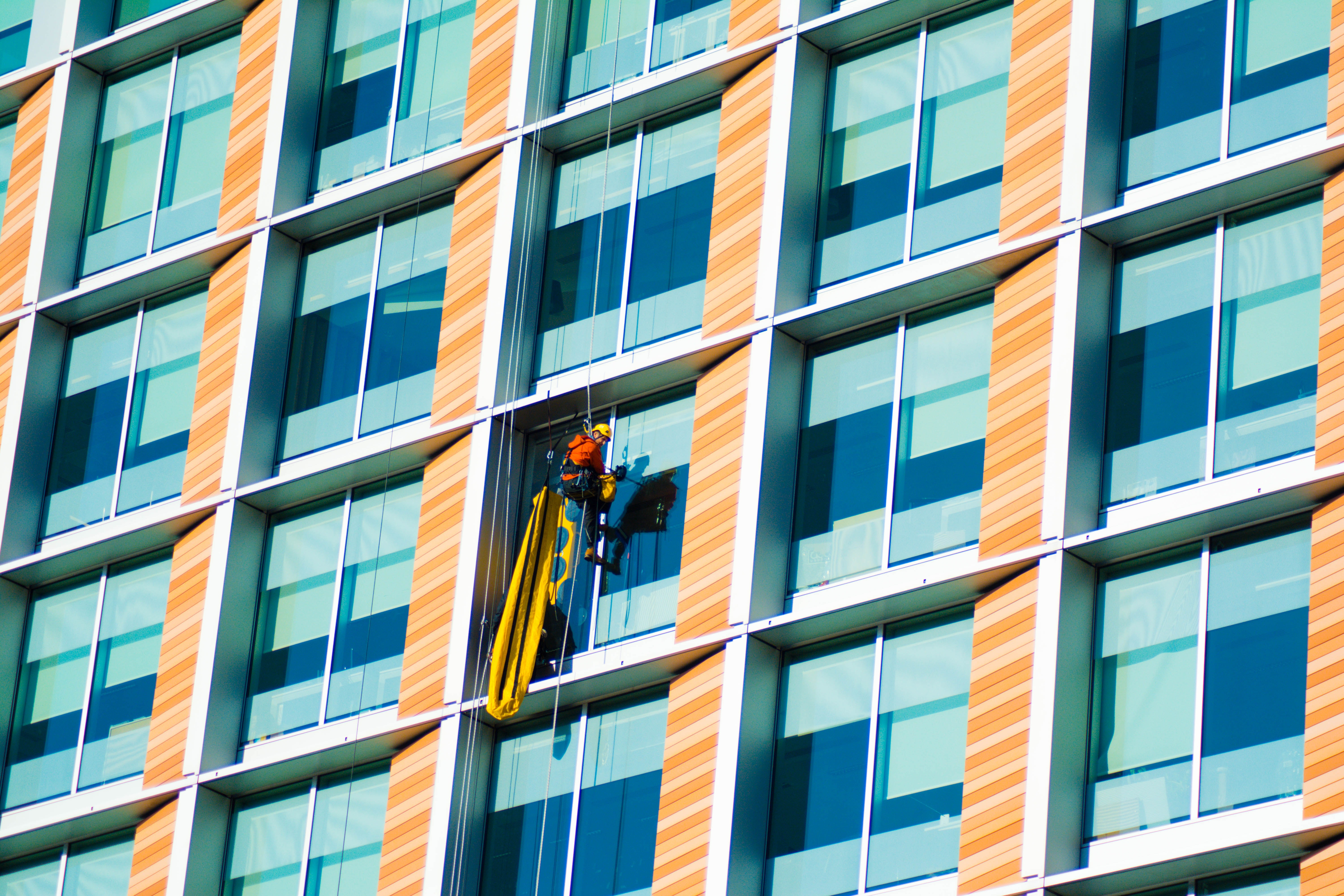A window cleaner on a rope near an office building window