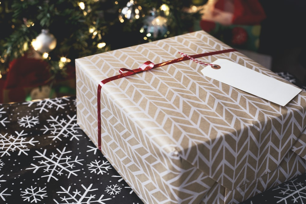 gold and white gift box on black and white fair-isle print surface