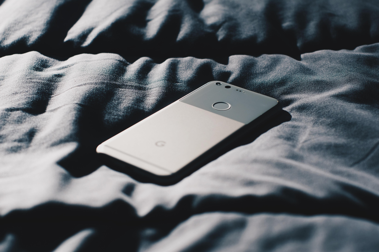 A black Google Pixel smartphone upside-down on a dark bed sheet