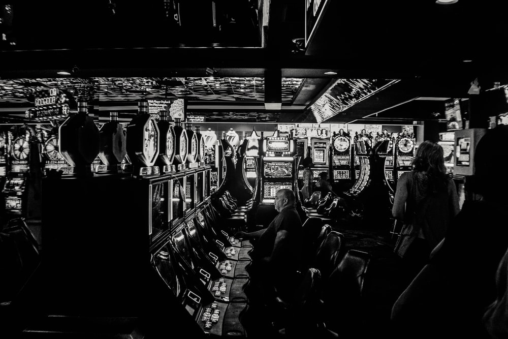 grayscale photo of man playing slot machine