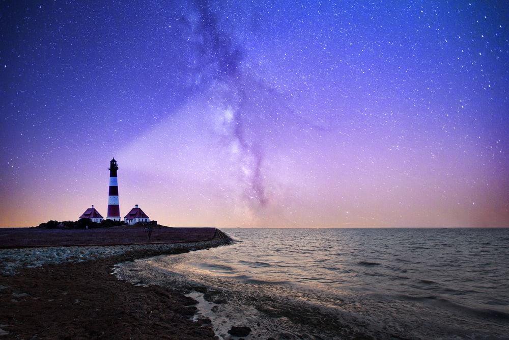 white and red lighthouse near bodies of water at night