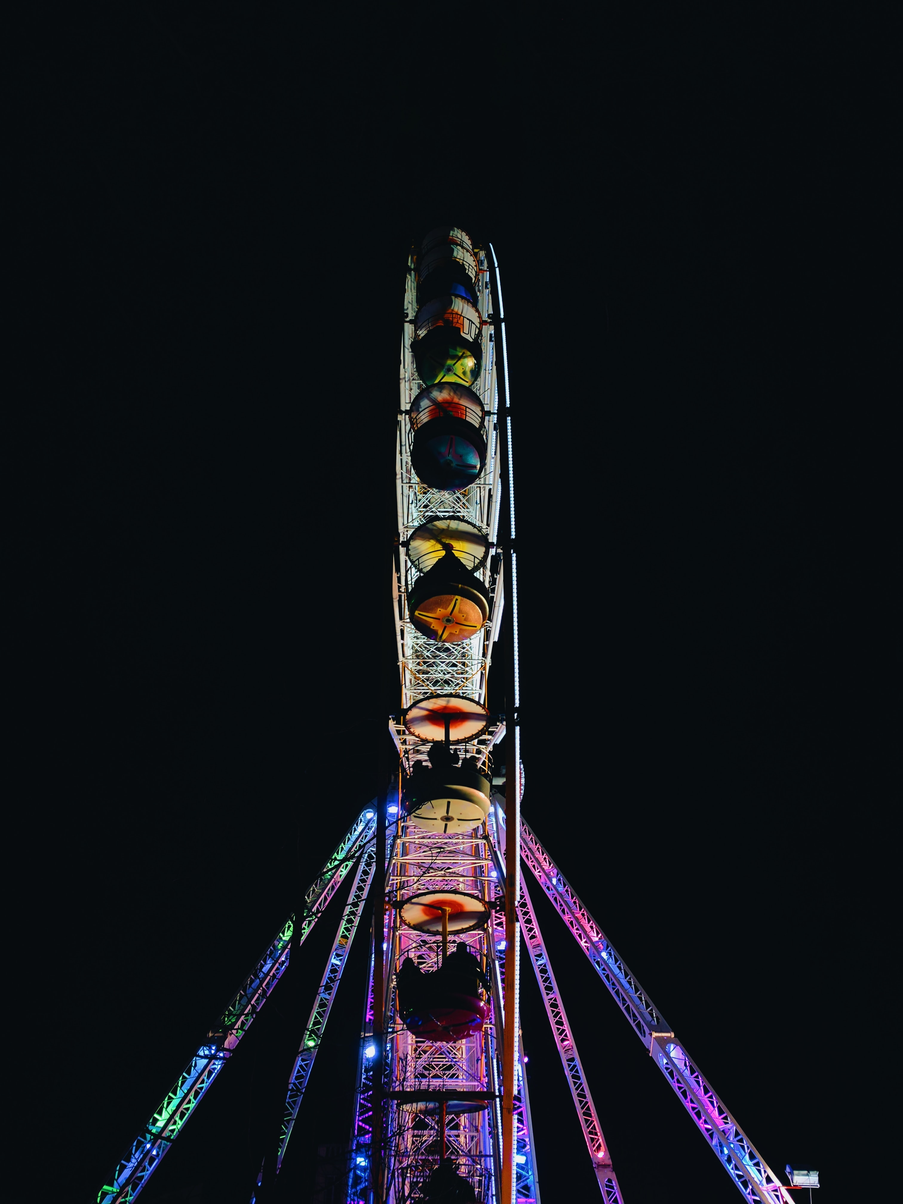 A Ferris wheel at a fairground lit up in bright colors at night