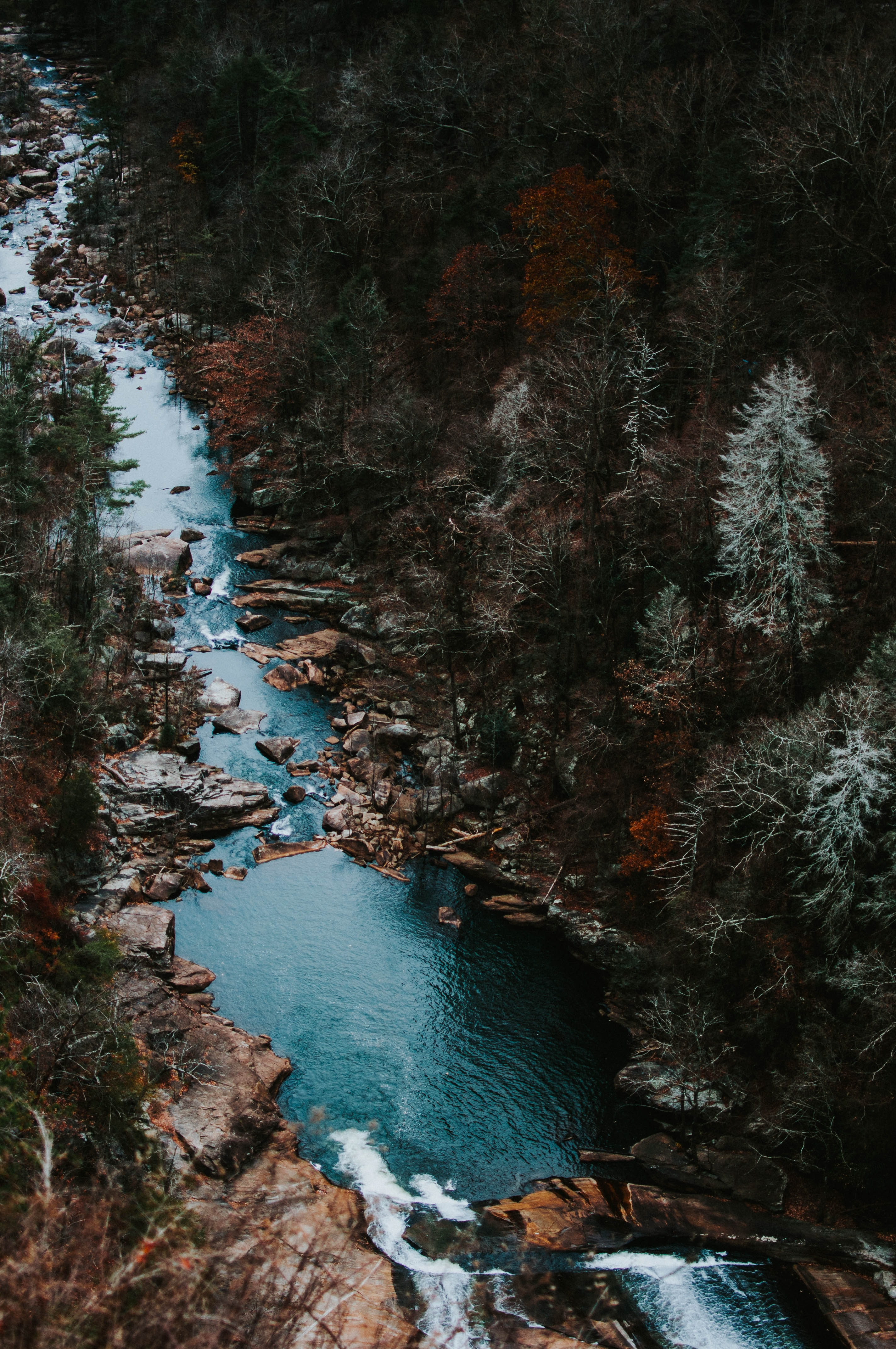 A drone shot of an azure stream on a rocky bed in a colorful autumn forest