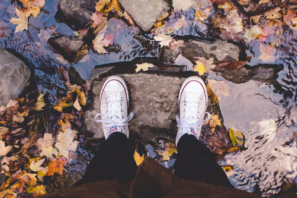 person wearing pair of white shoes standing on rock