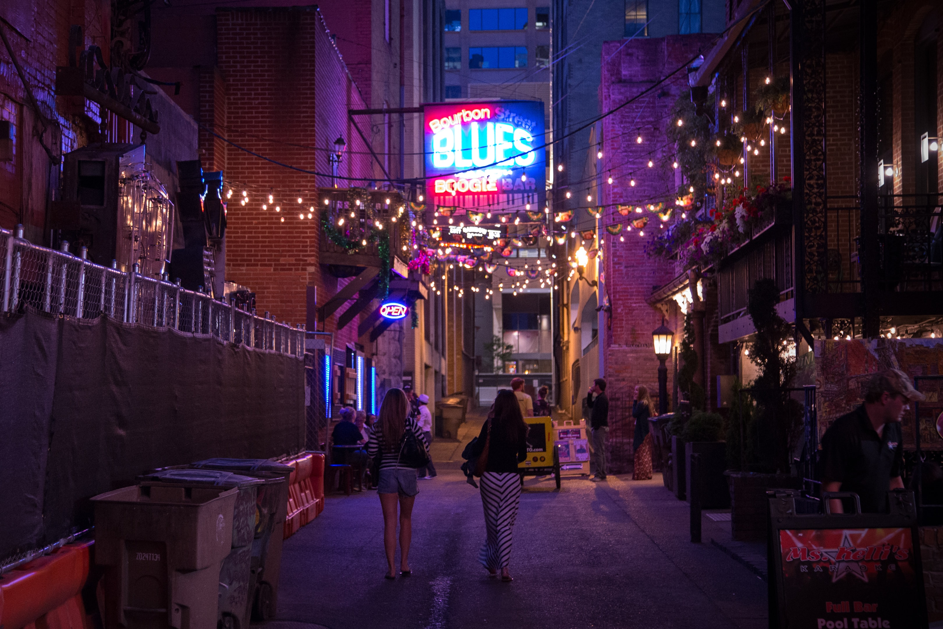 People walking through a downtown street under a line of lights.