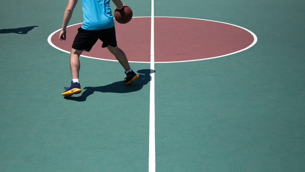A man wearing yellow Nike sneakers dribbling a basketball on a green and red basketball court at Queens Quay West