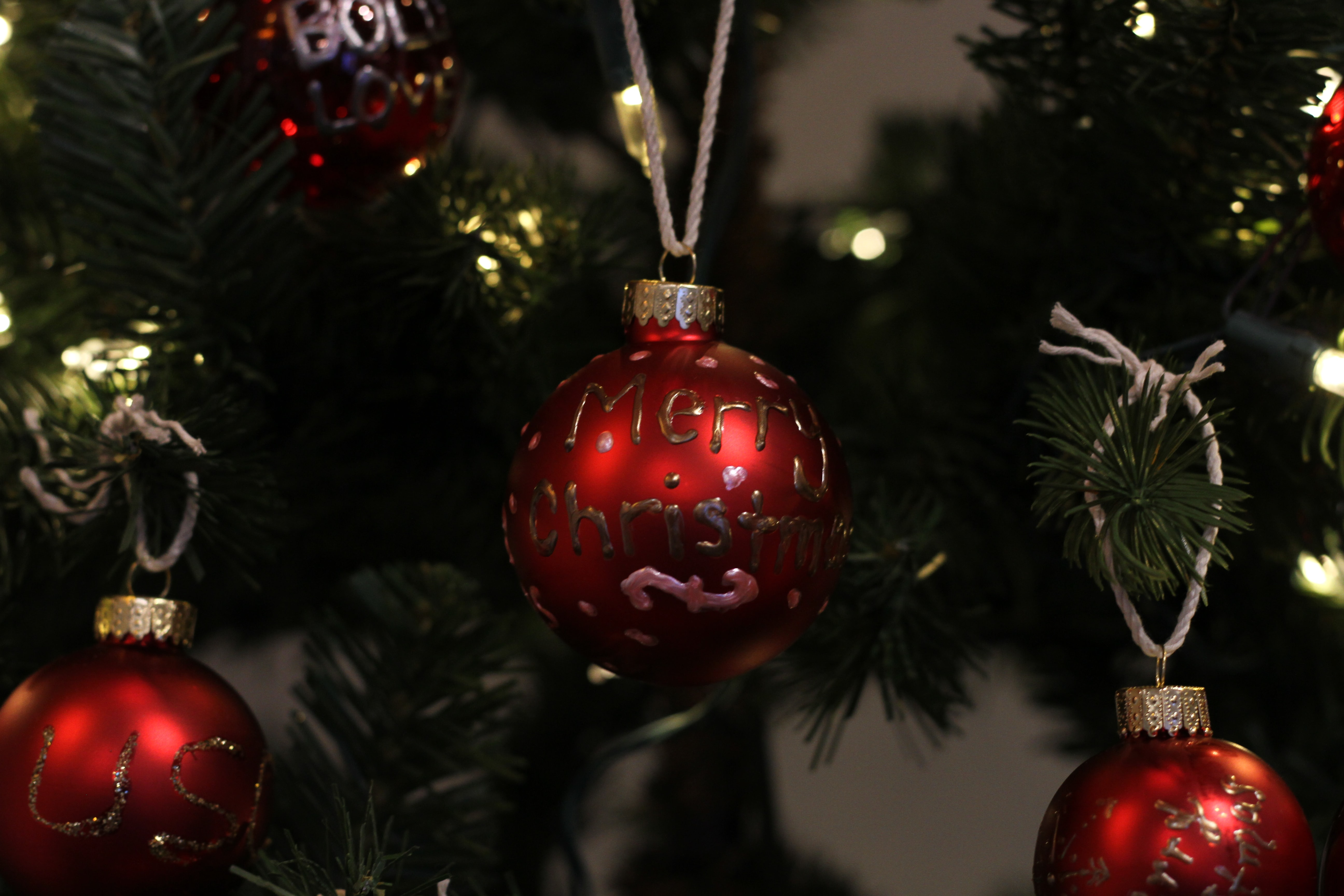 Red ornaments hanging from a Christmas tree.