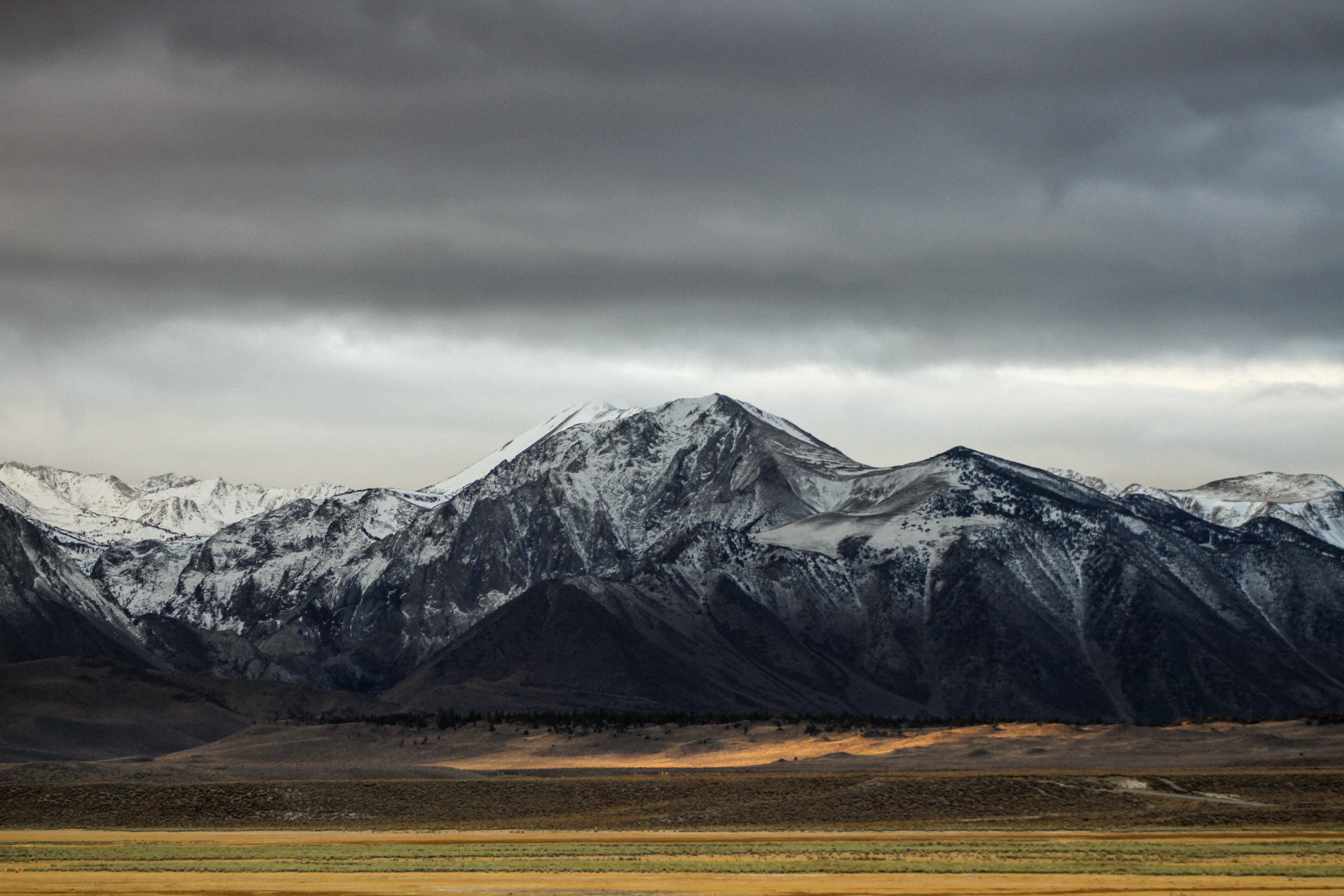 Barren plains stretching below snowy mountains