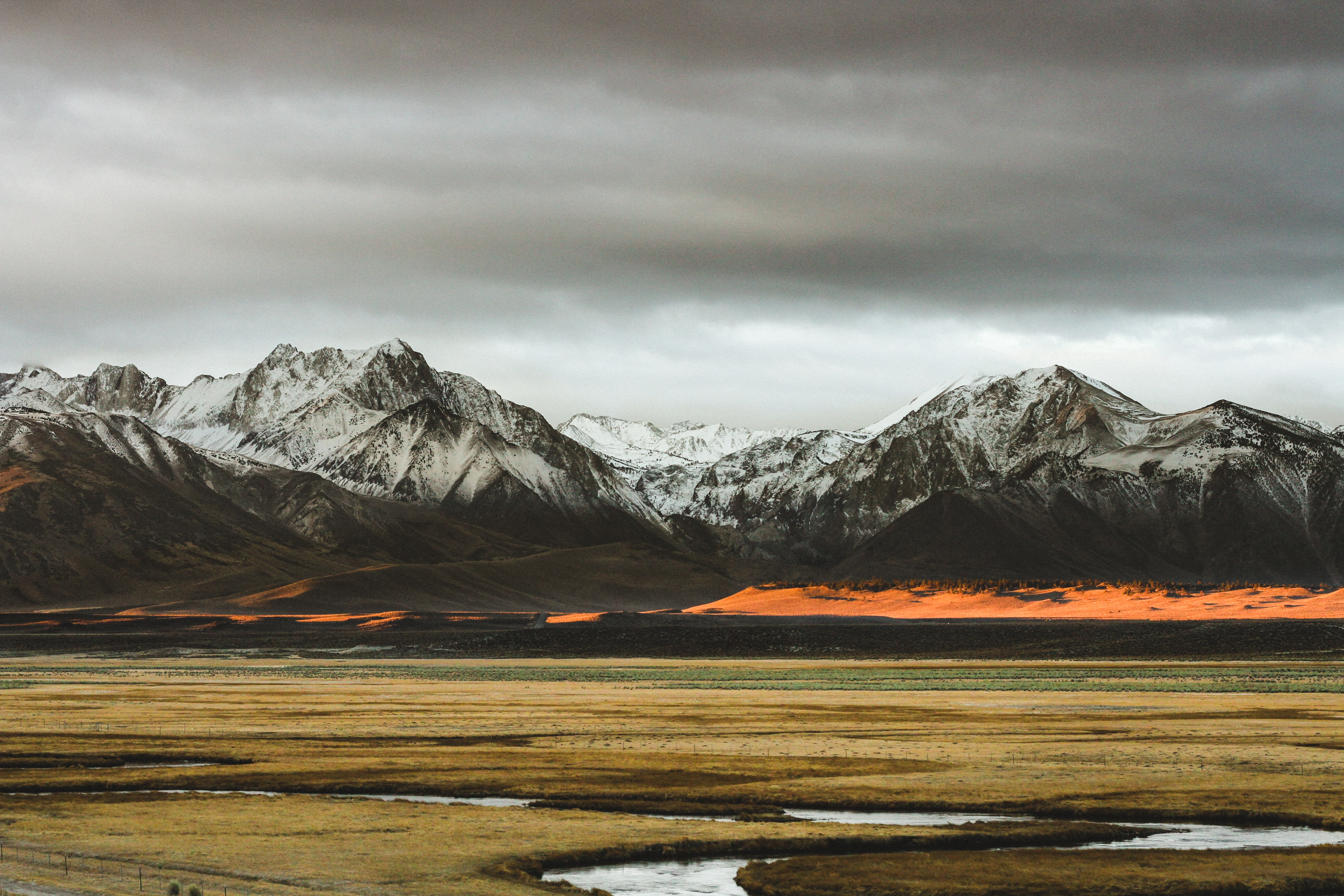 A stream flowing through the plains at the foot of a mountain range on a cloudy day