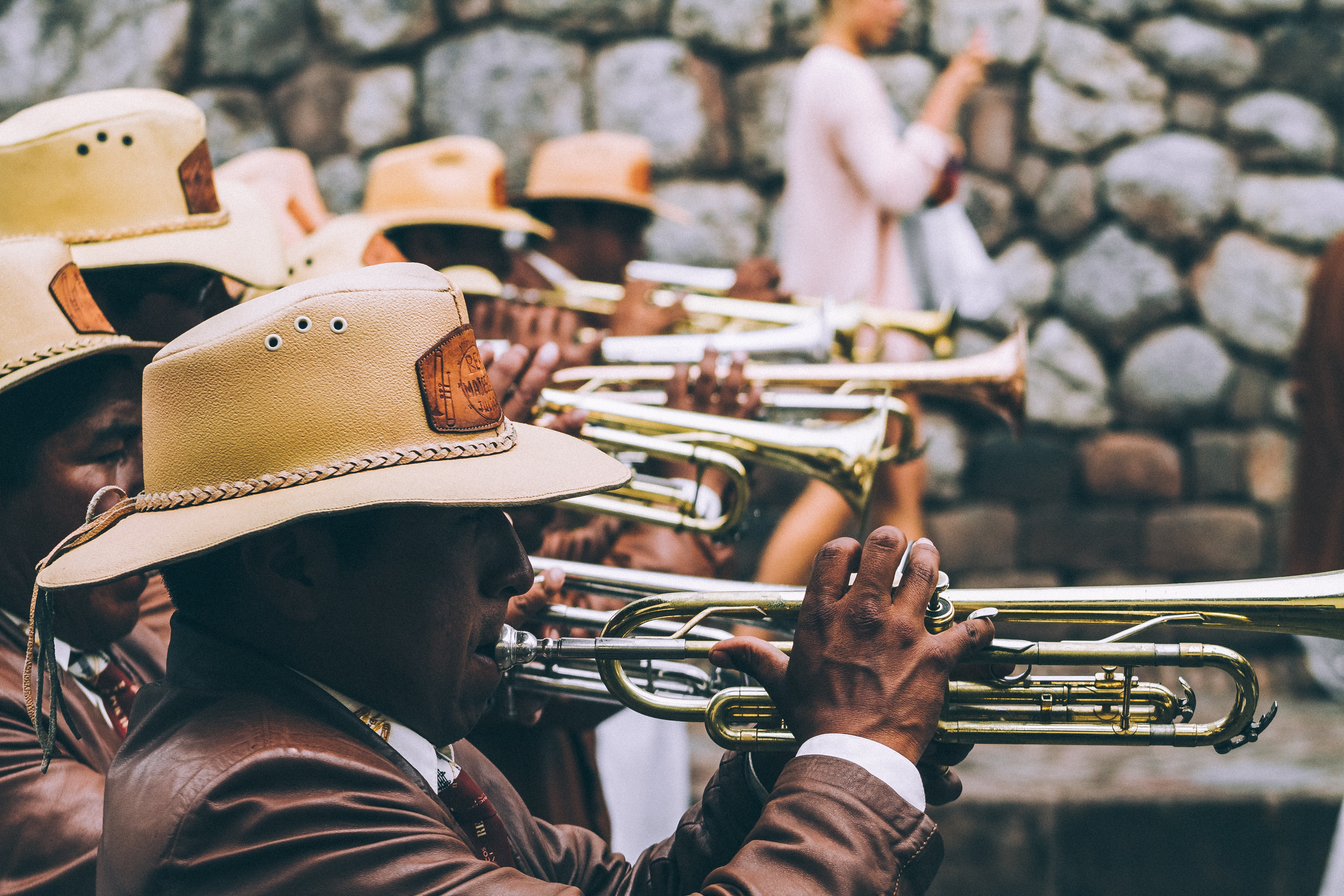 Trumpets players in uniforms are playing in a marching band on the street.