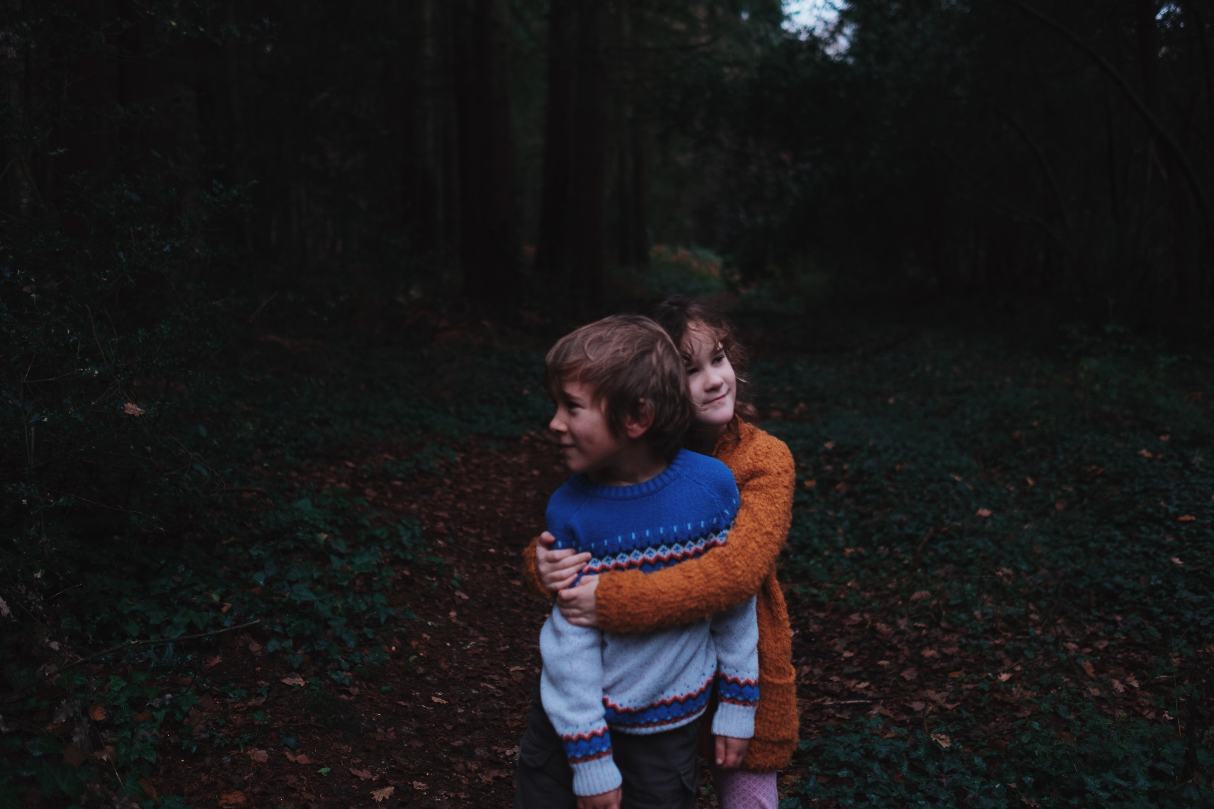 A young girl squeezes a boy in a giant hug