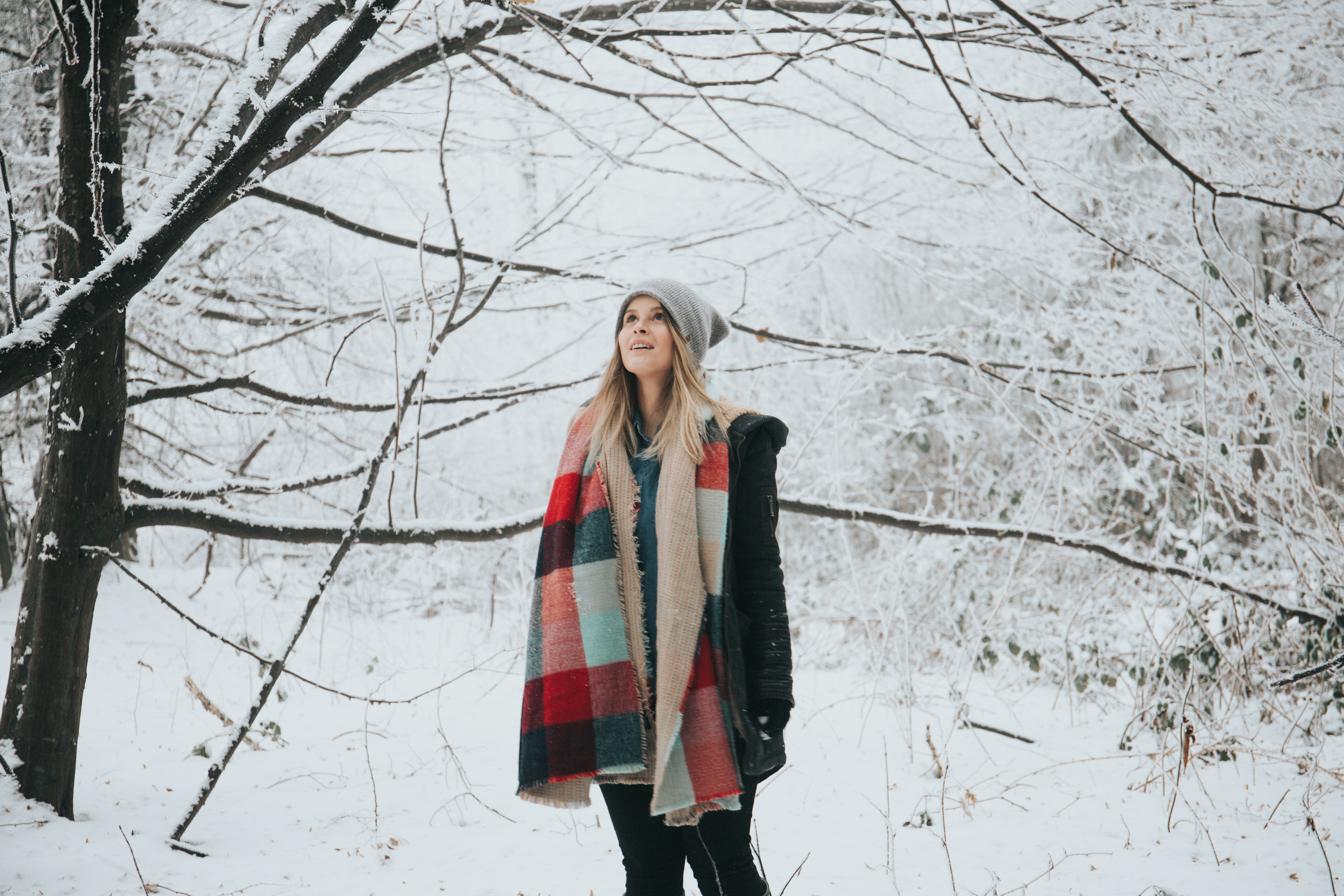 Happy woman in a hat and scarf stares in awe at snowy trees