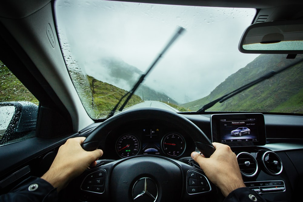 person driving Mercedes-Benz car during daytime