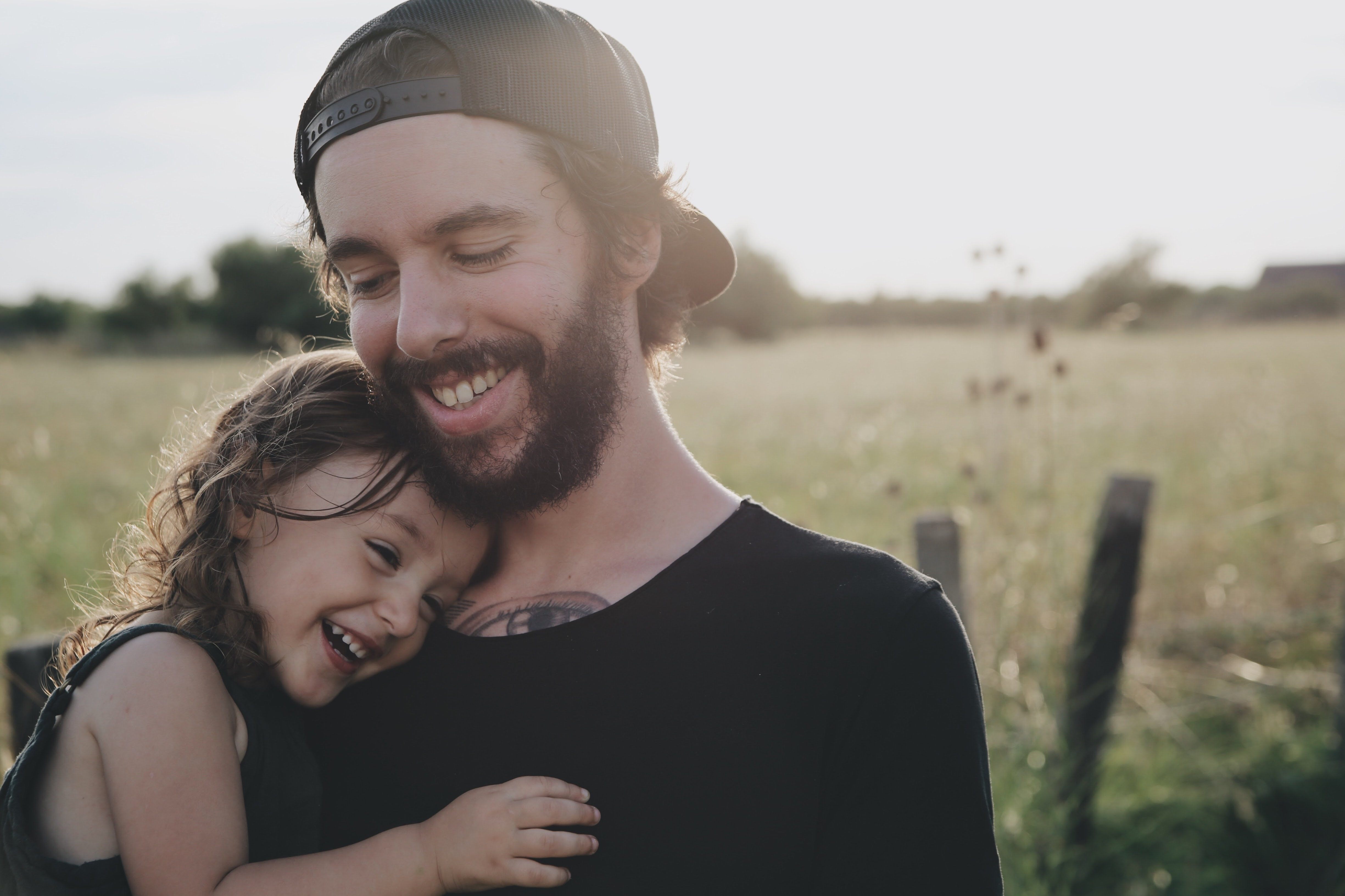 Man with a beard, tattoo and black shirt holds a laughing girl in a field in the sun