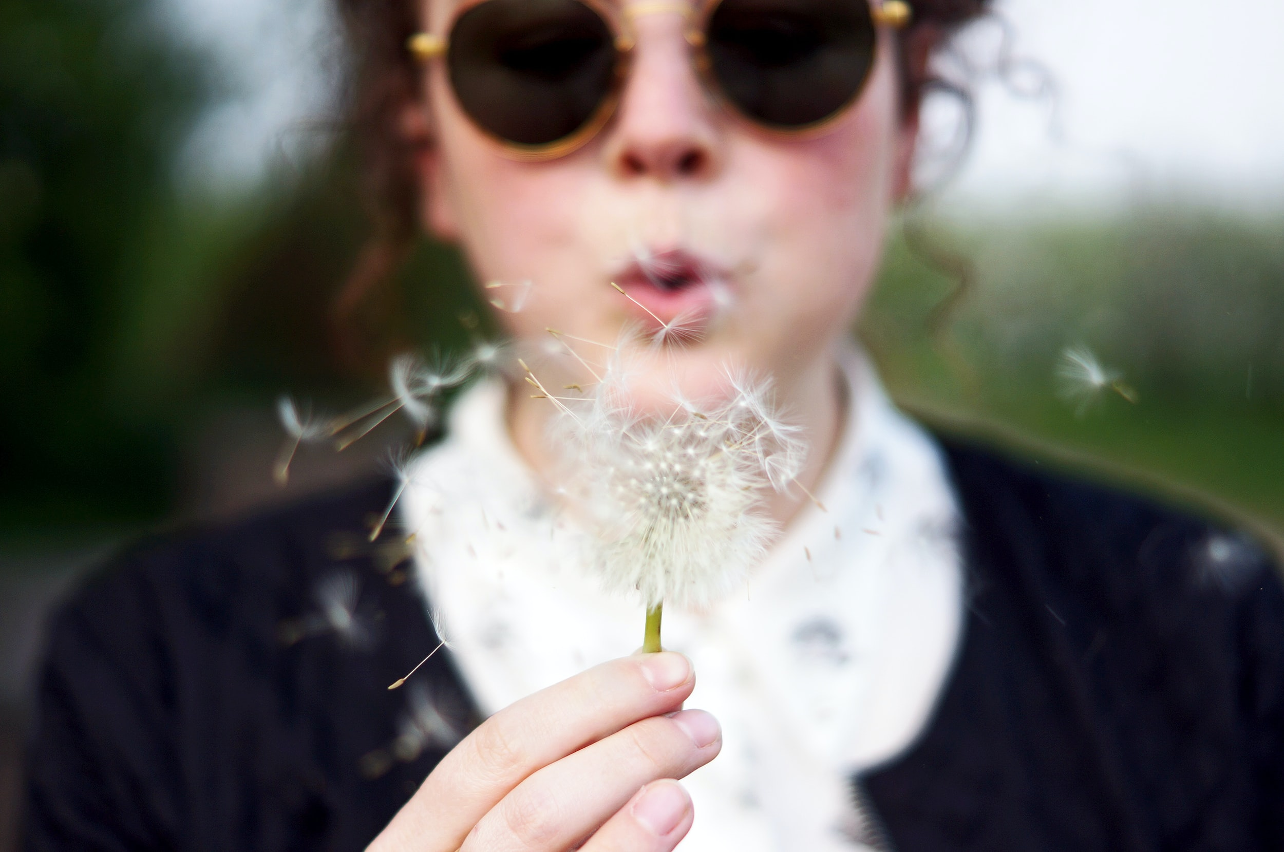 A woman blowing at a dandelion seed head