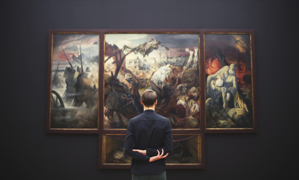 man hands on back looking on painting mounted at wall