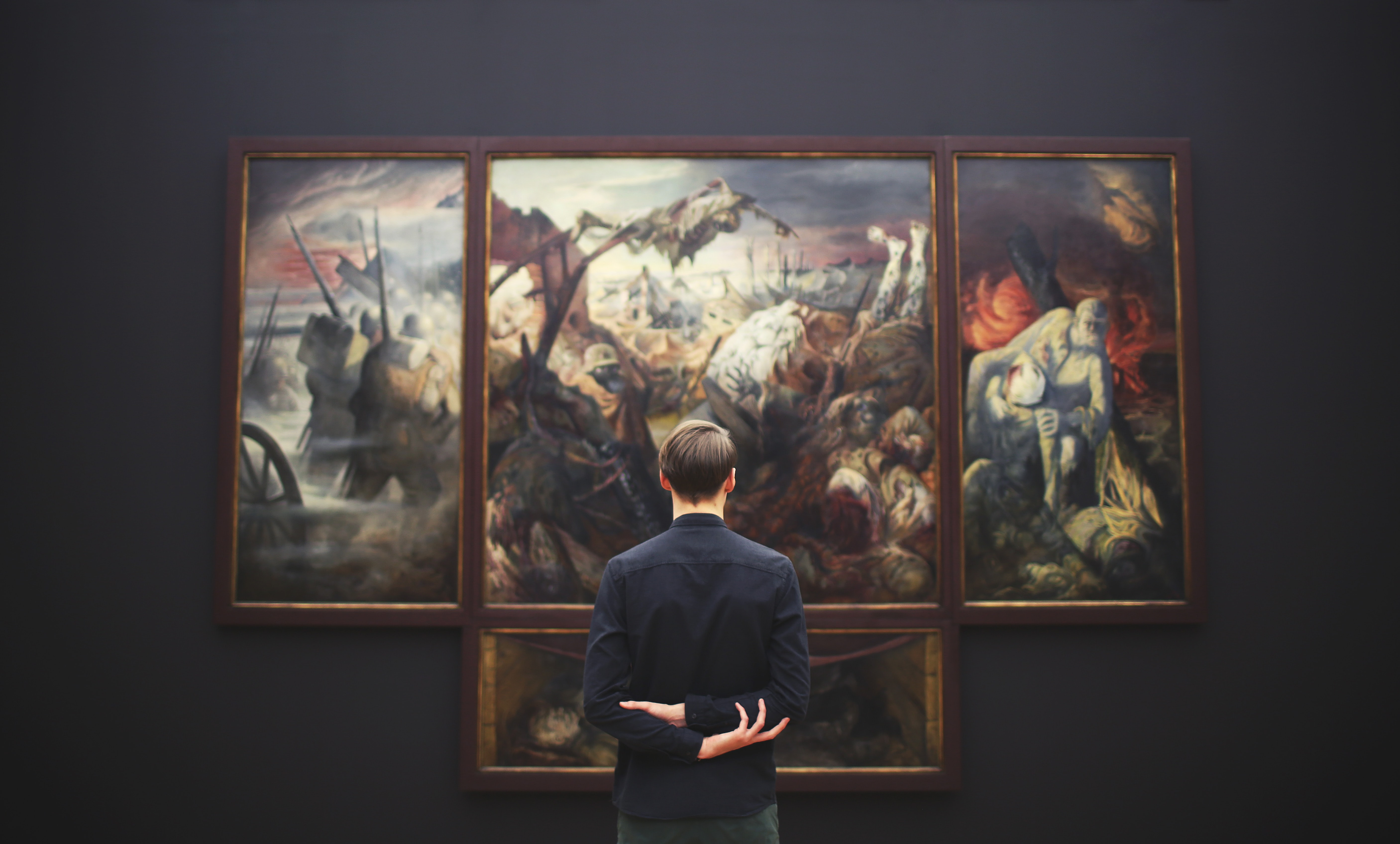 Wide angle shot of a man from behind, who is looking at a large painting in a museum.