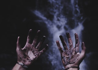 person hands with black liquids