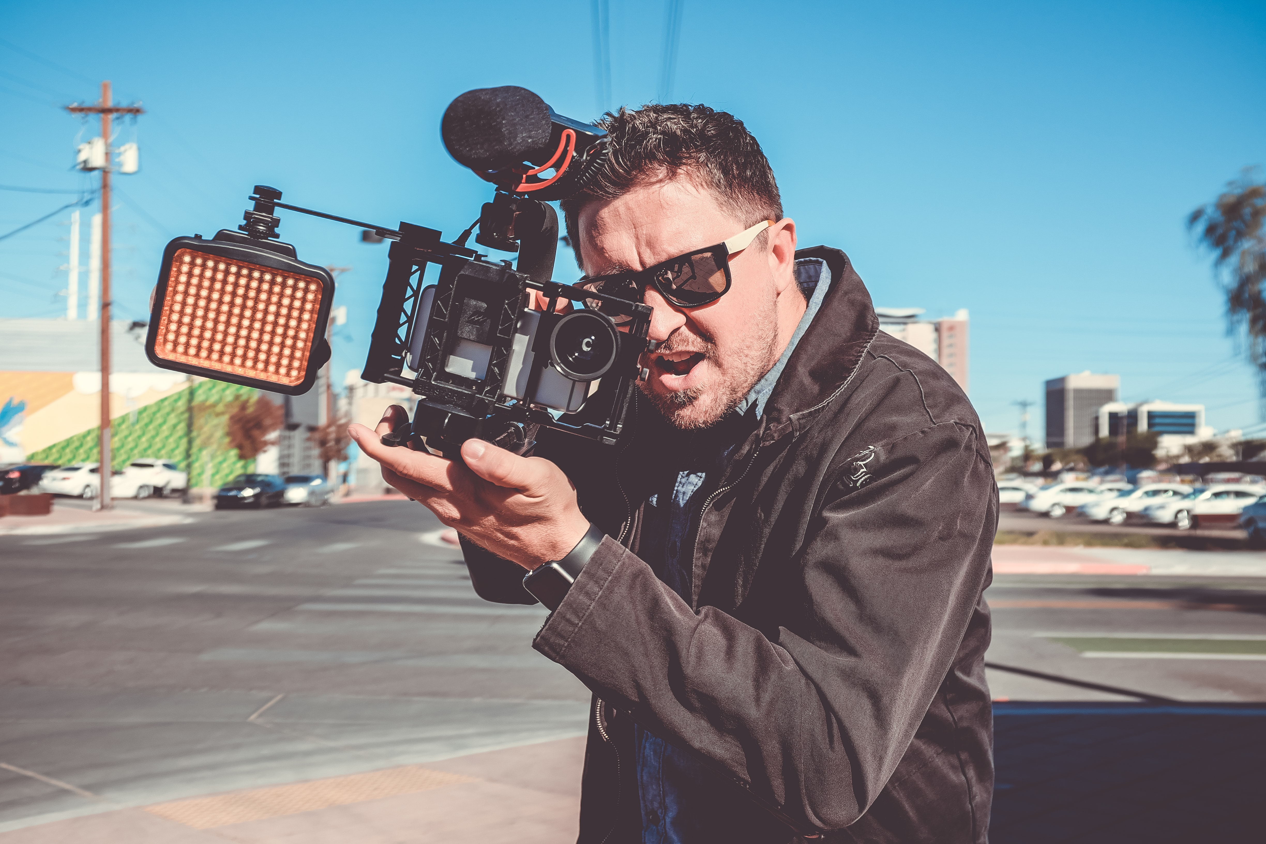 A man in sunglasses holding a professional camera with an excited expression on his face
