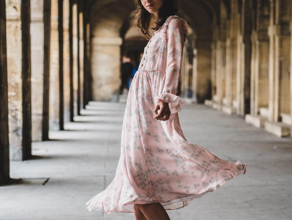 woman wearing pink long-sleeved dress standing inside building