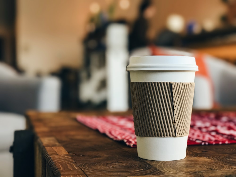 white plastic cup on brown surface