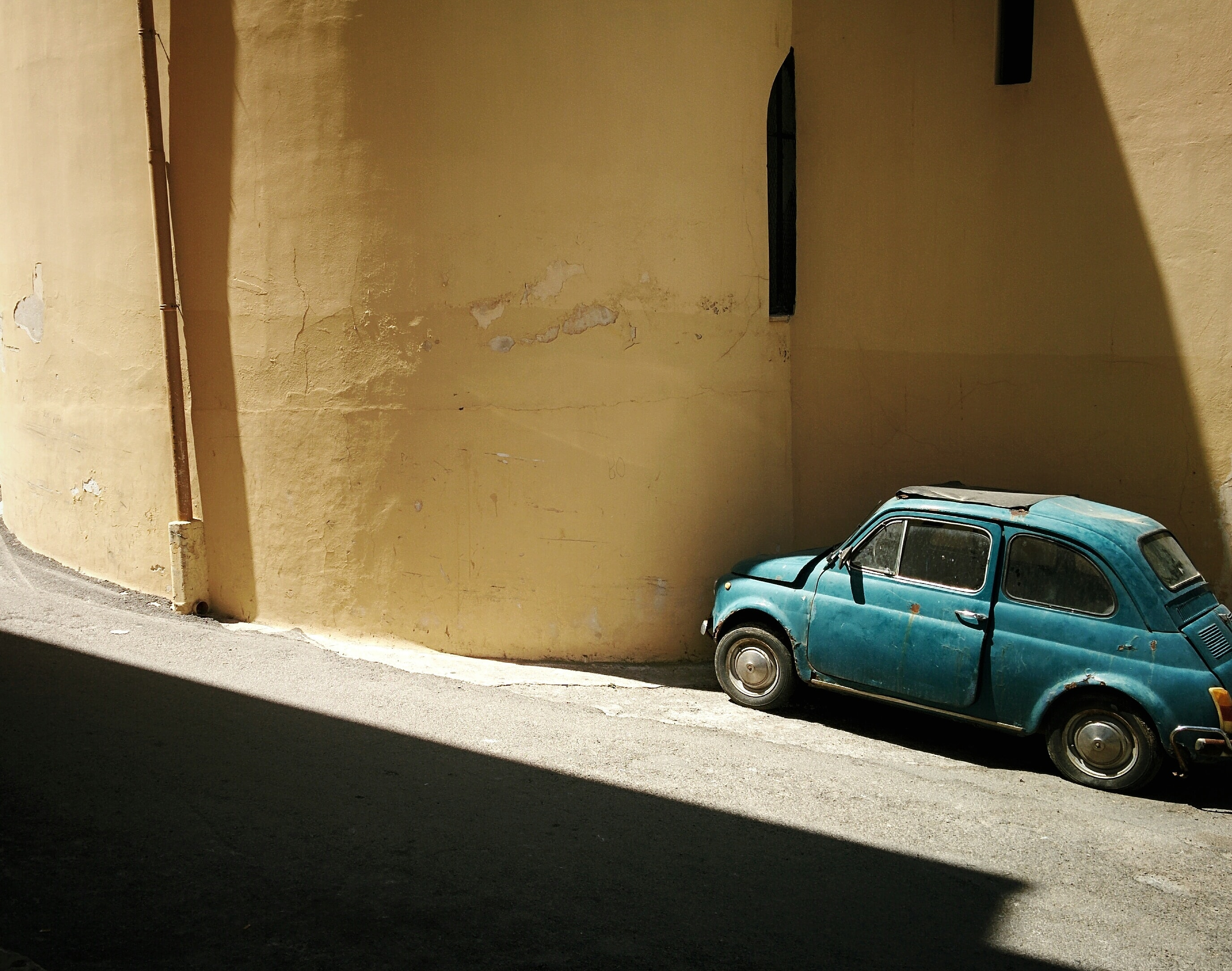 A rusty blue vintage car parked near a wall in Palermo