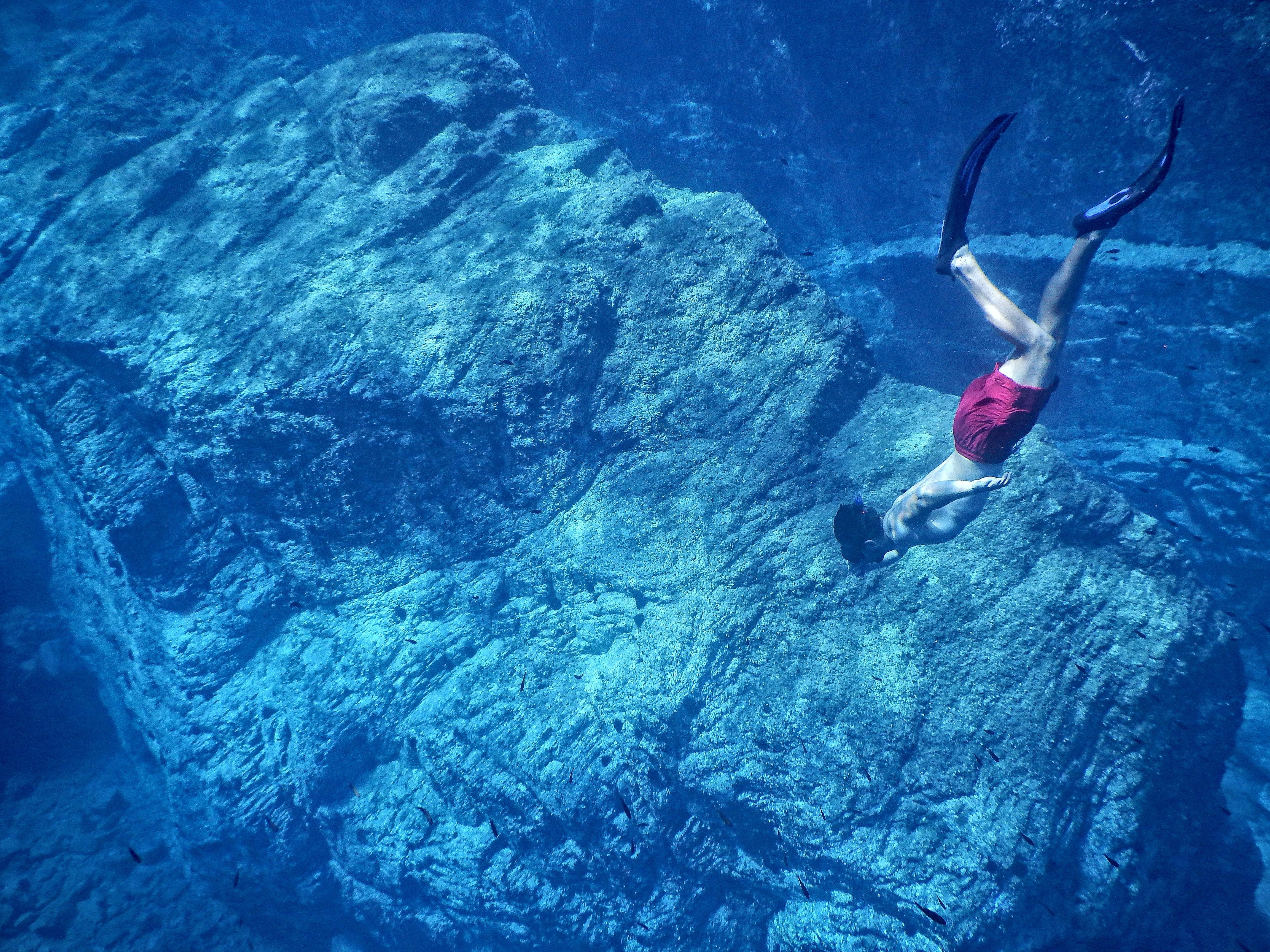 man in red shorts swimming near huge underwater rock
