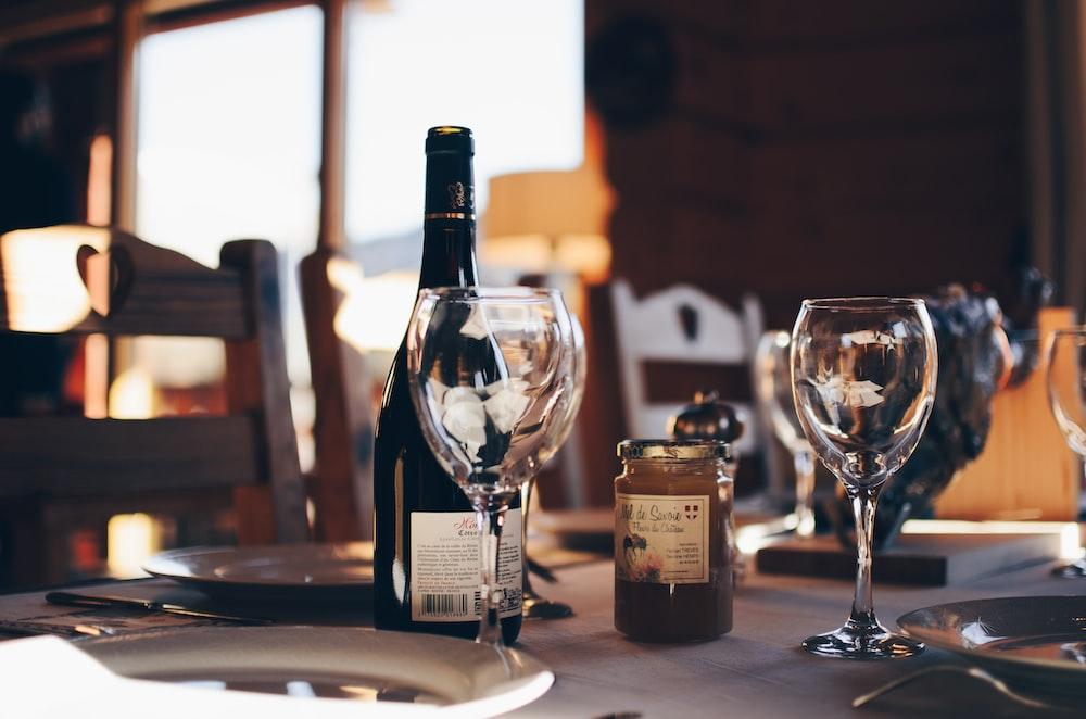 closeup photo of two empty wine glasses beside wine bottle