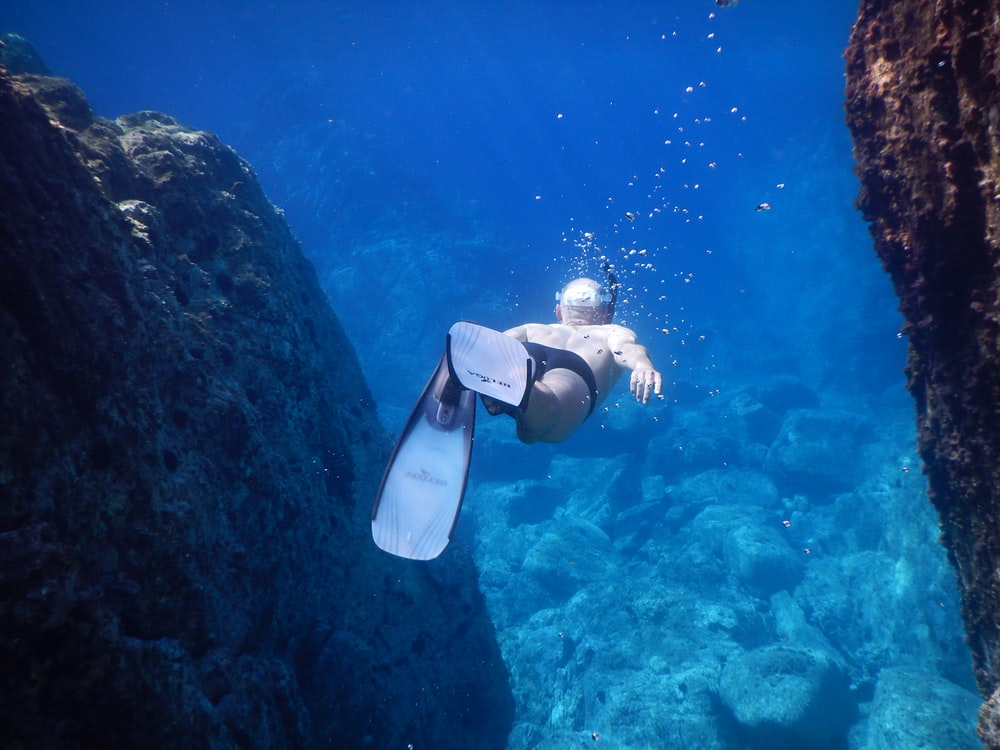 underwater photo of person wearing flippers