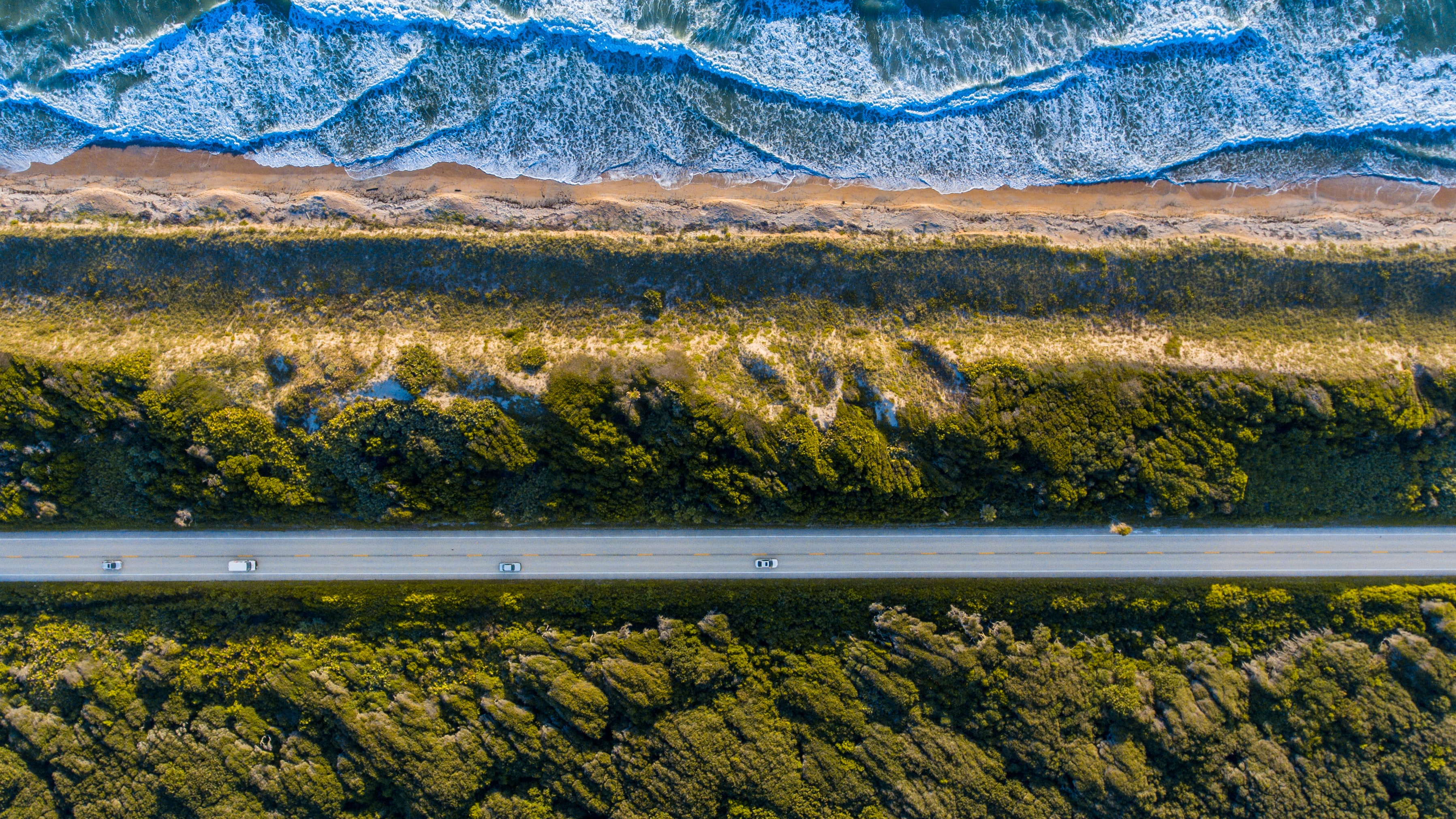 A drone shot of cars on a straight road by the ocean