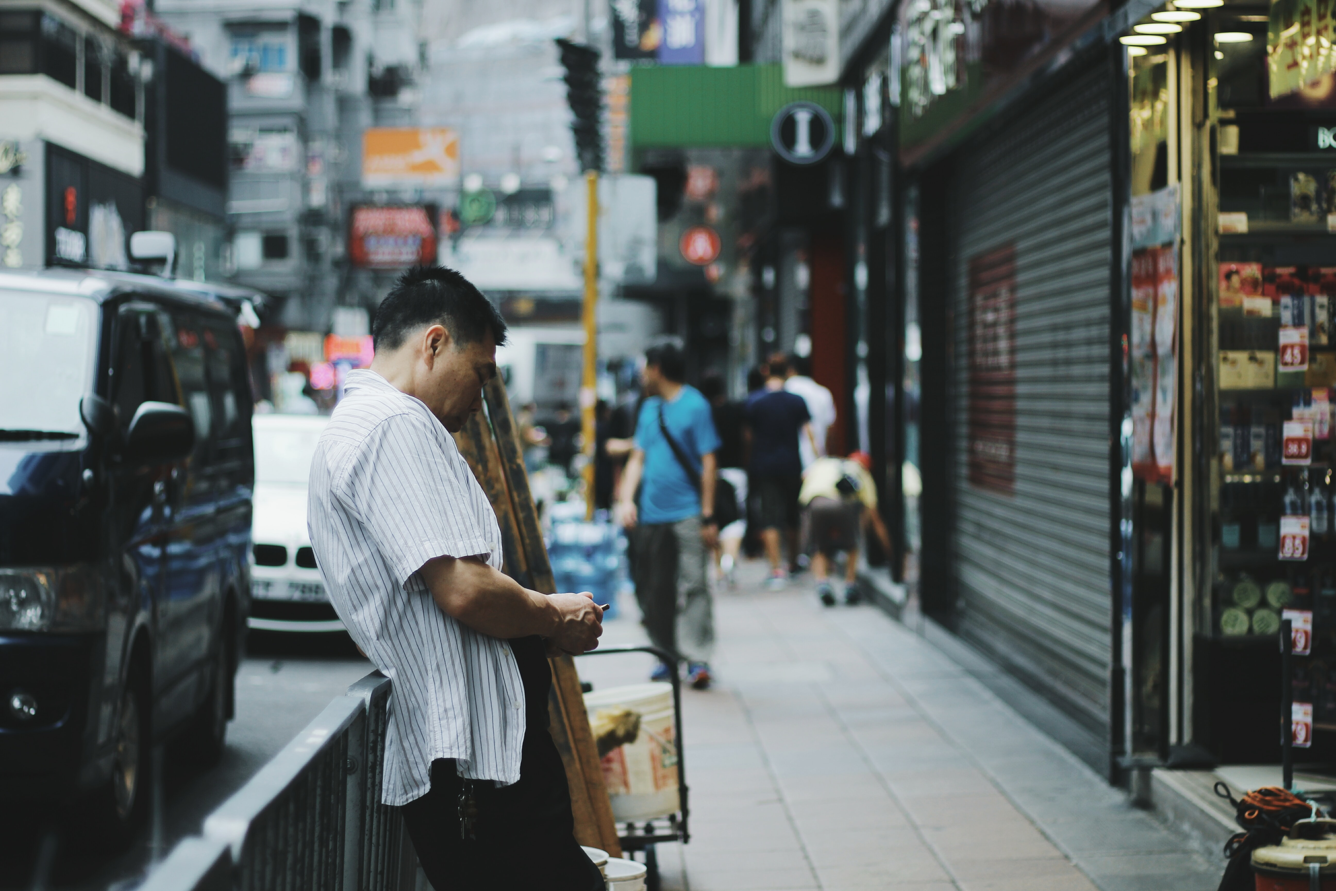 A man on the sidewalk looks down aside a city street and shops in Hong Kong