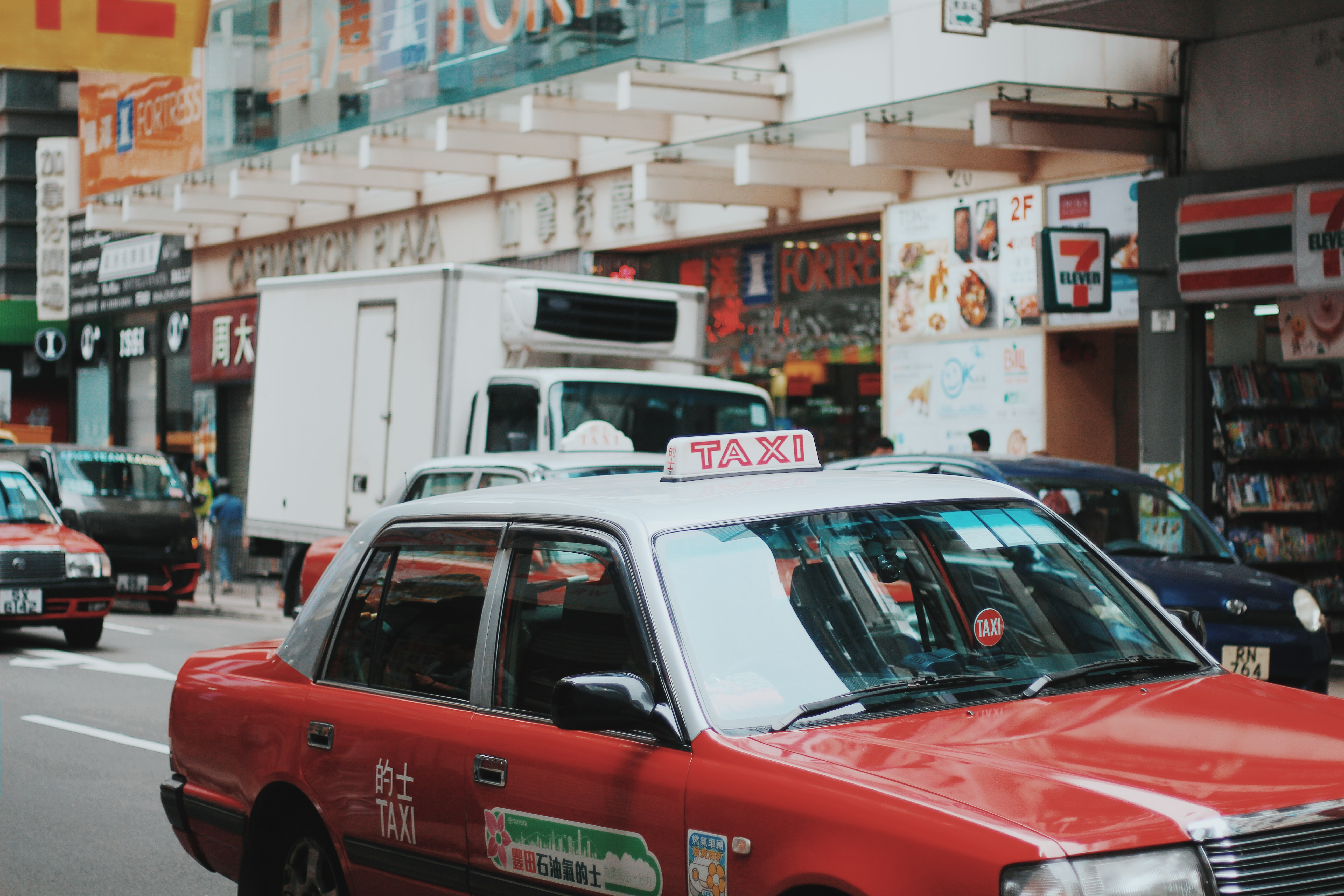 Red and white taxi car in a busy urban street in Tsim Sha Tsui