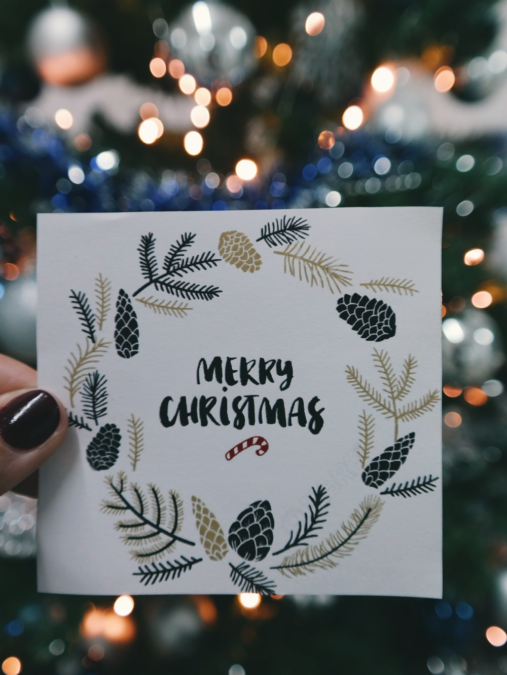 "A piece of paper that says ""Merry Christmas"" with a wreath around it, being held up in front of an XMAS tree."