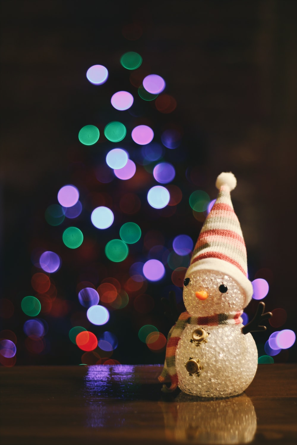 A little snowman figure sitting on the floor in front of a Christmas tree.
