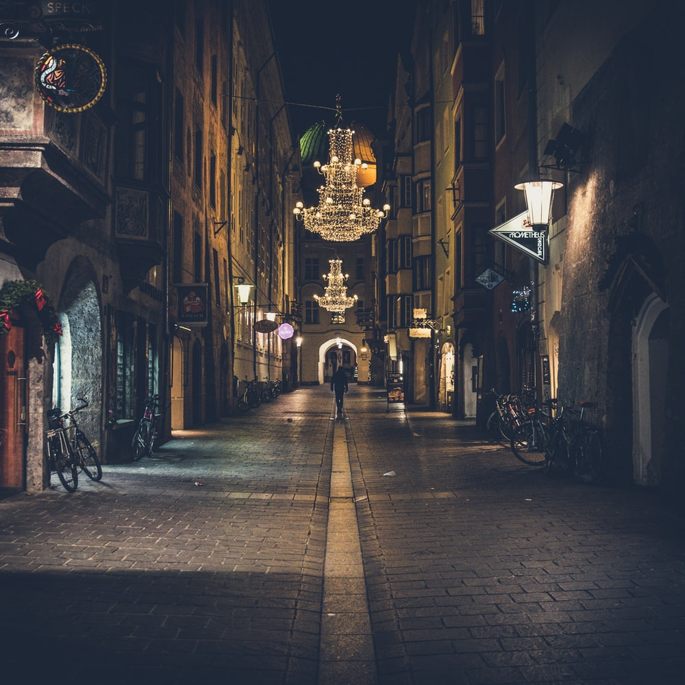 person walking on pathway showing lighted chandelier during night time