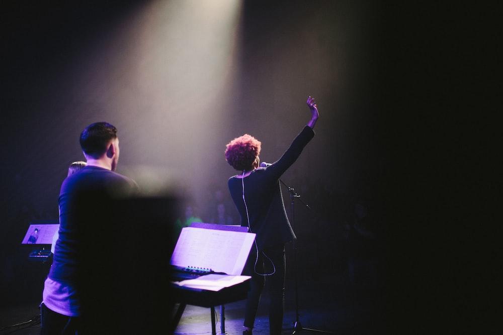 woman raising her hand beside microphone