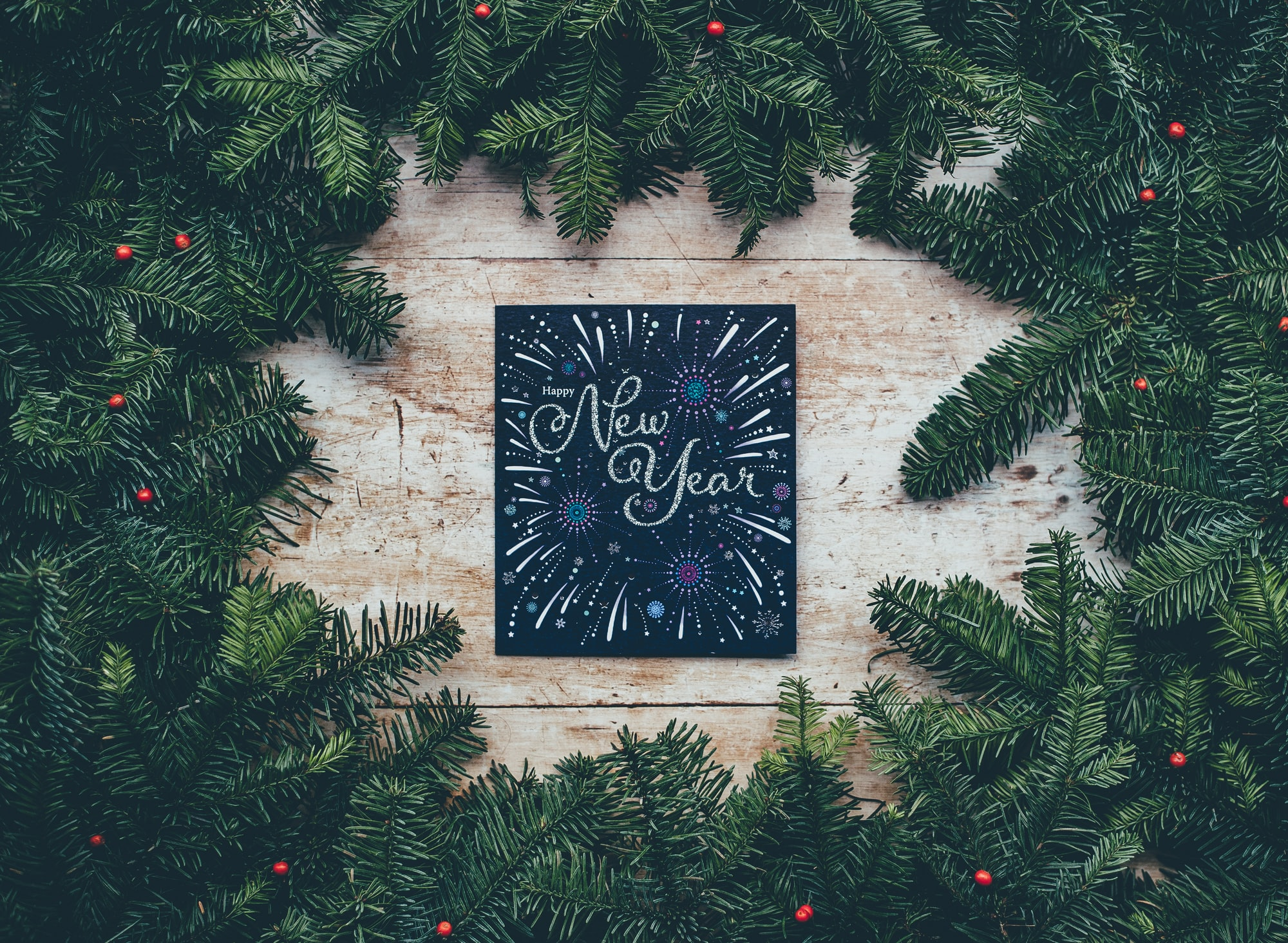 """A handpainted sign reads """"Happy New Year"""" and is surrounded by pine tree branches."""
