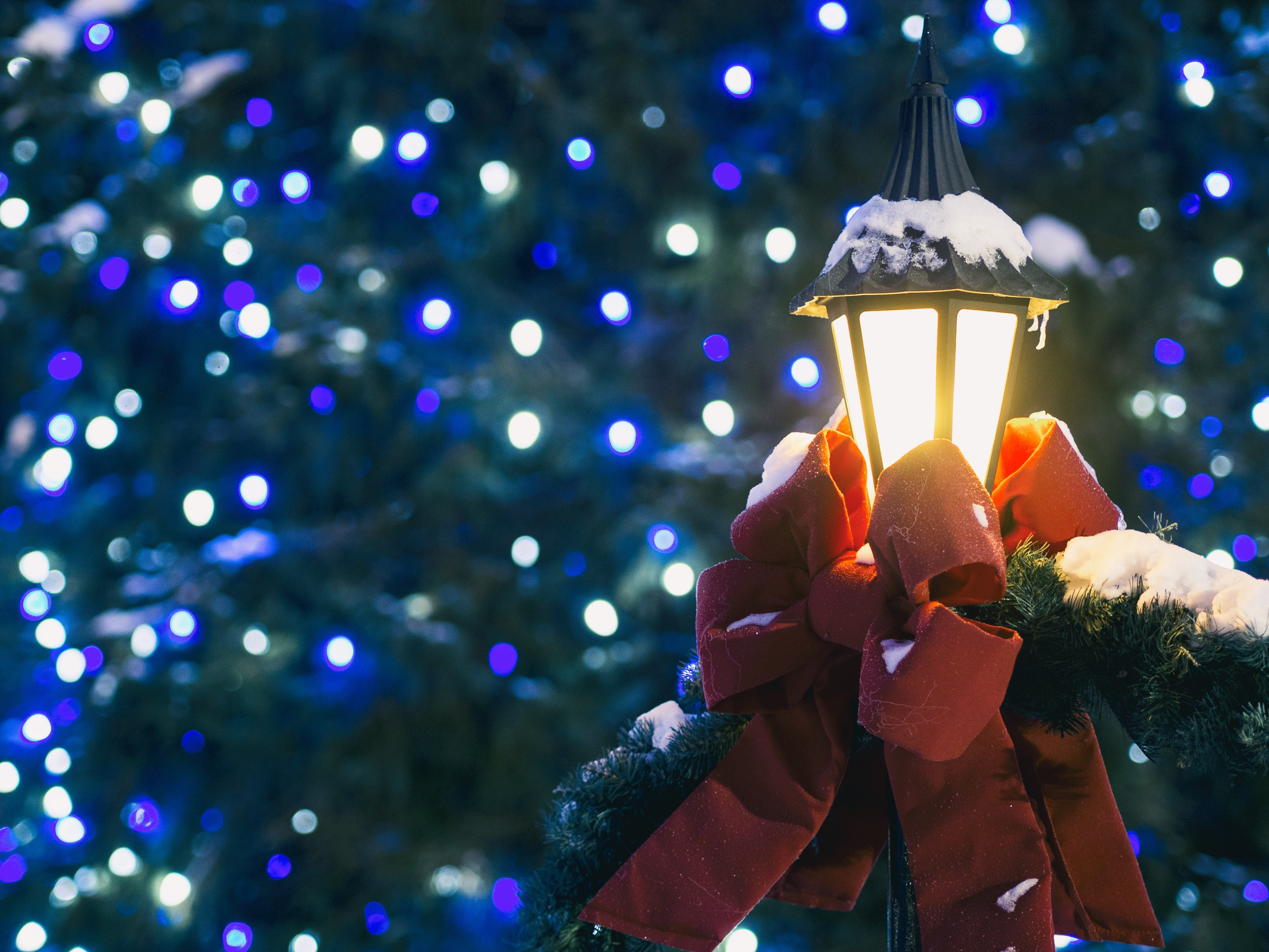 A lamp decorated with a red ribbon in front of a bokeh of blue Christmas lights