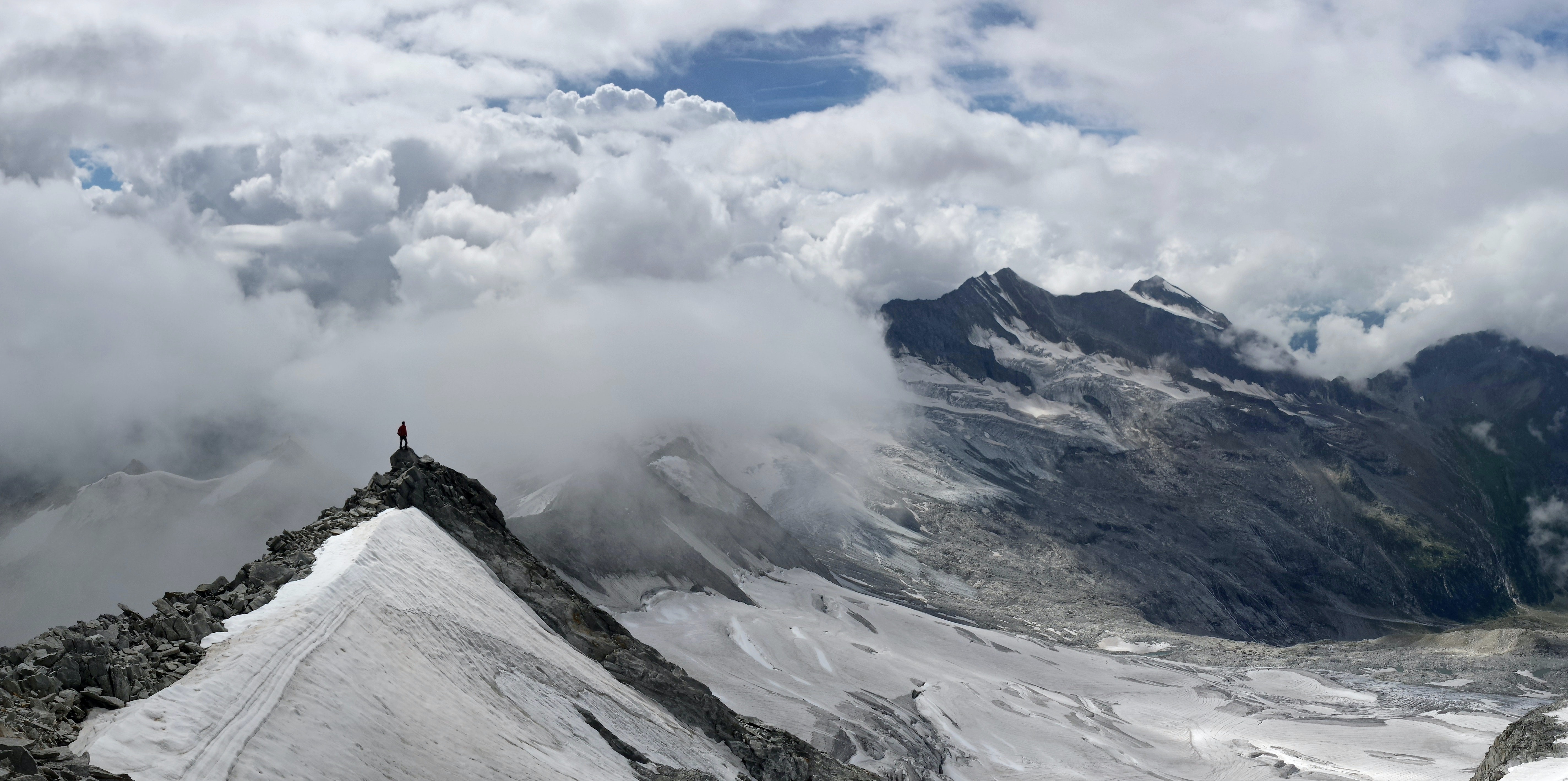 Clouds cover snowy mountains where hiker surveys the scene