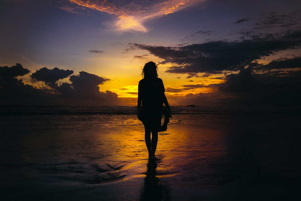 silhouette of woman standing on seashore