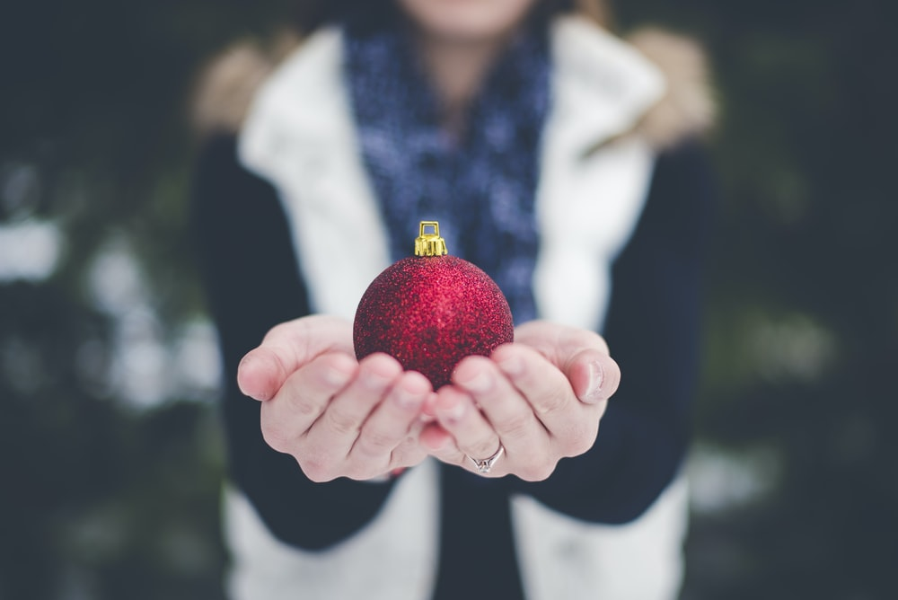 shallow focus photography of person holding bauble