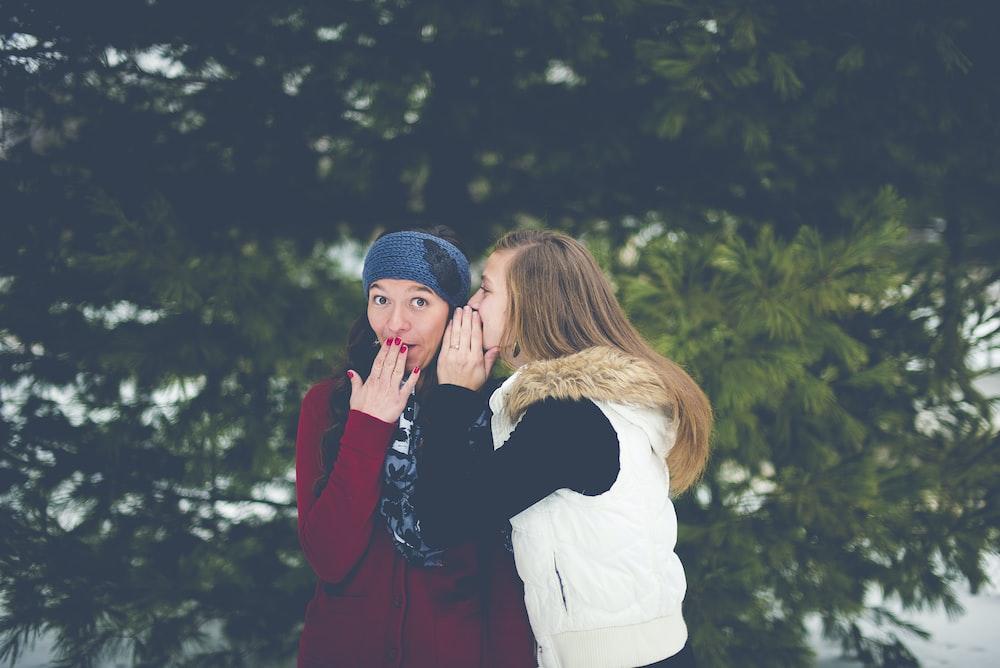 女性の唇に手をしながら女性の耳にささやく