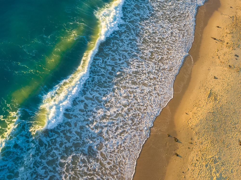 aerial photo of green and white sea with foam on shoreline at daytime