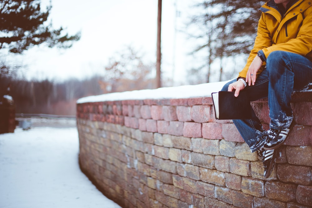 A person wearing jeans and a yellow coat holds a book while sitting on a wall in the snow.