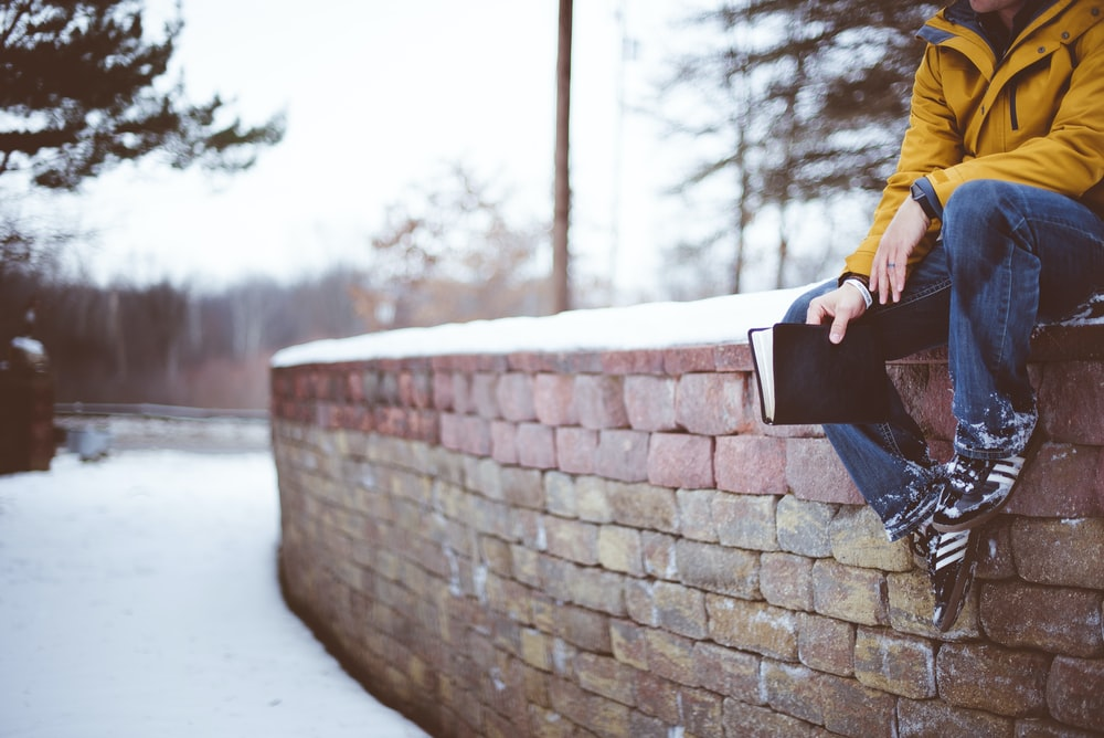 person sitting on brick wall