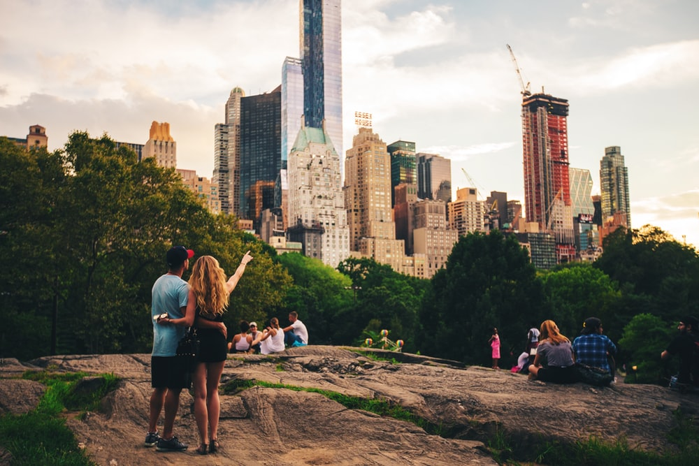 man and woman standing on hill looking at s skyscraper