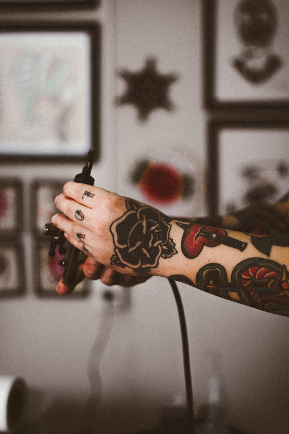 shallow focus photography of person holding black tattoo machine