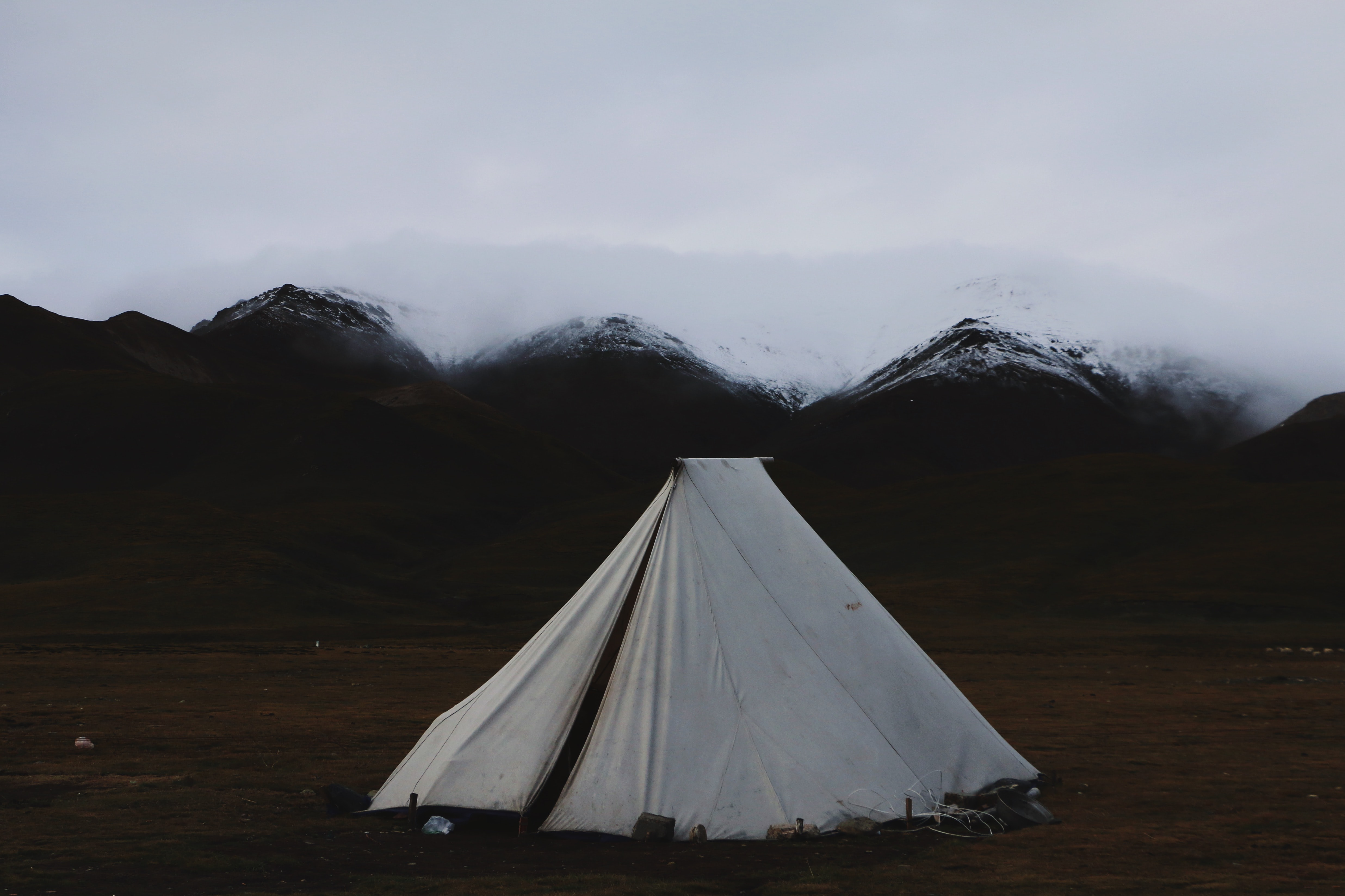 White tent set up in the grass with snowy mountains in the background