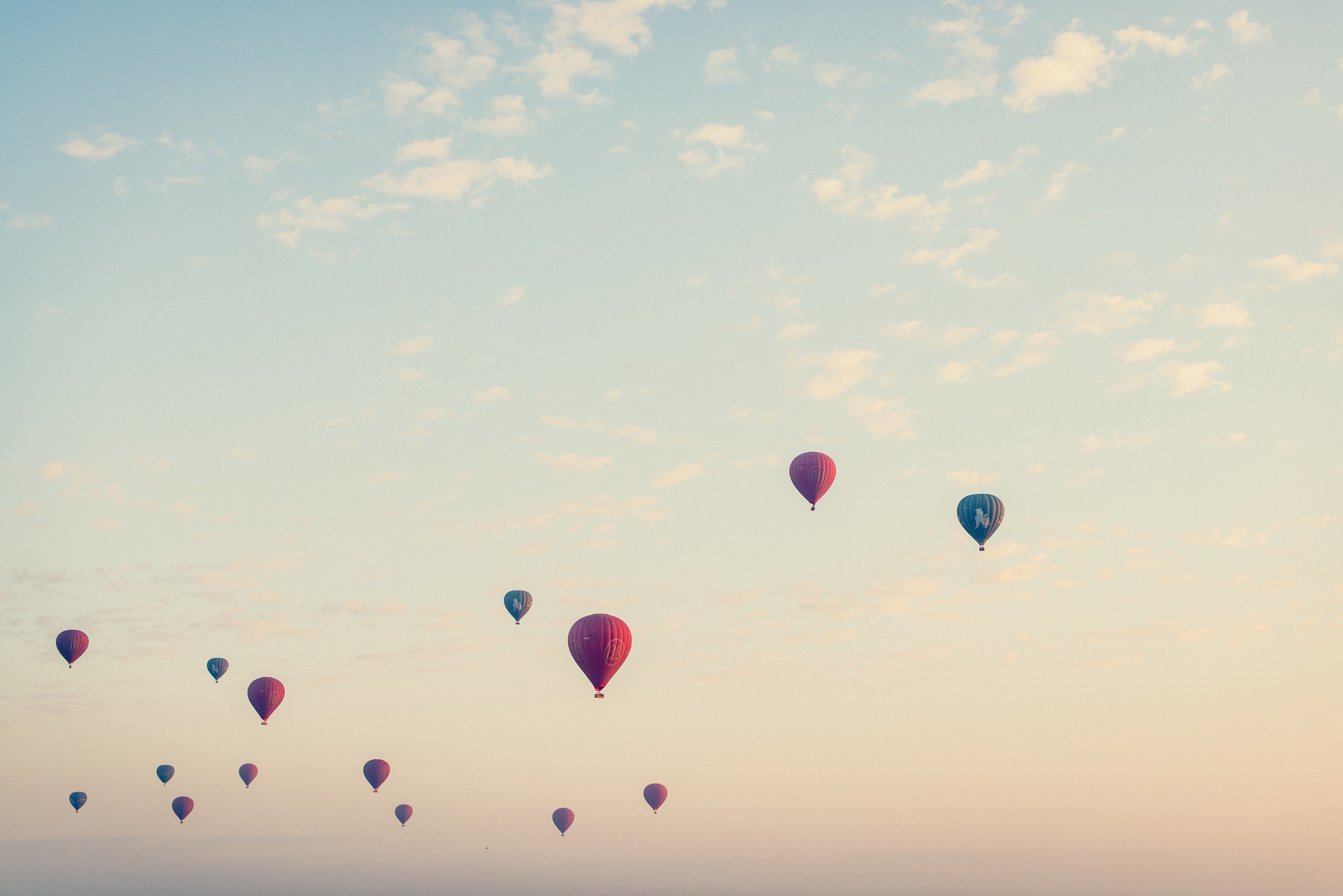 Several hot air balloons with different colors flying into the sky in old began.