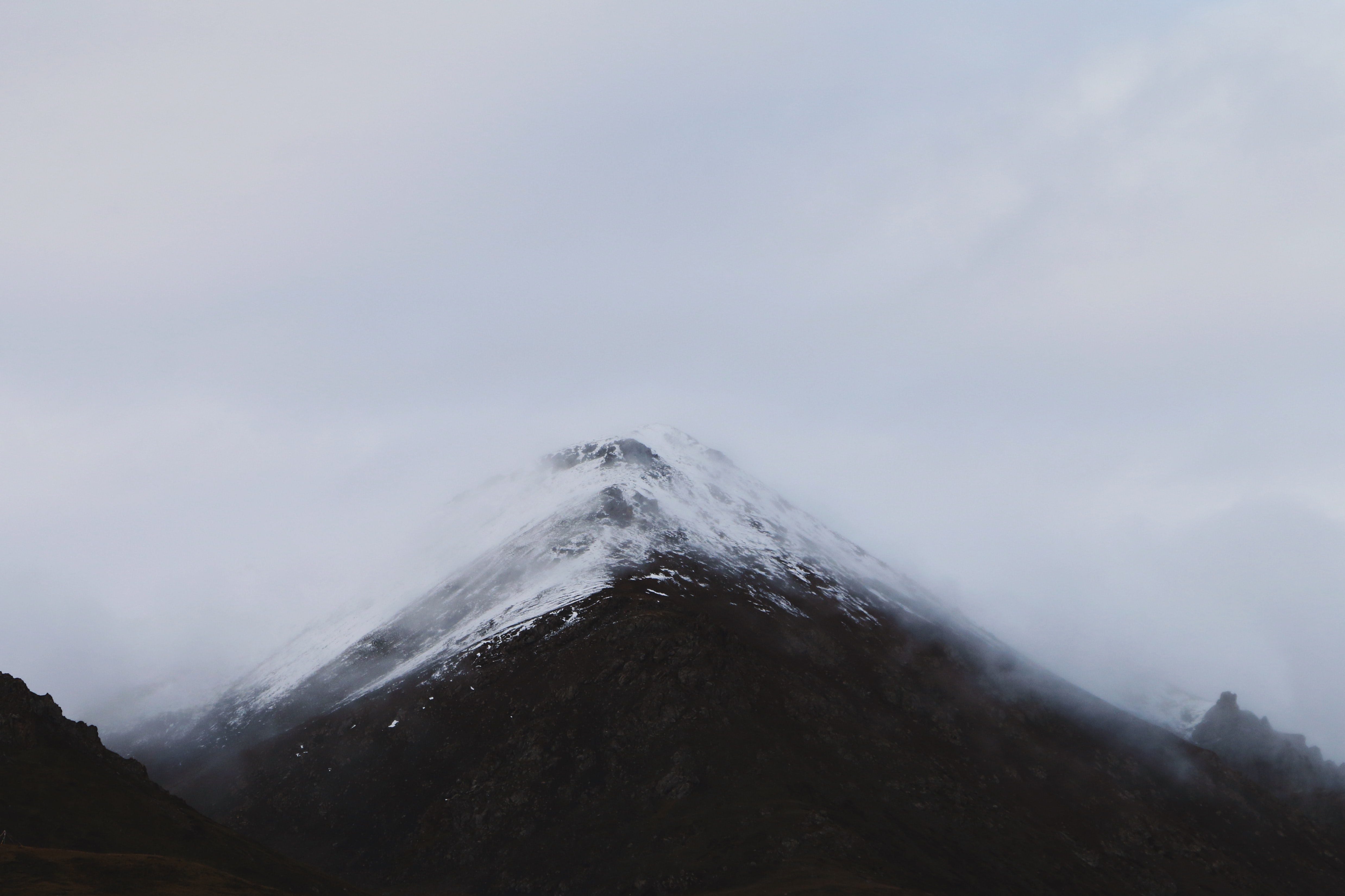 Snowy summit of a mountain covered by fog and clouds